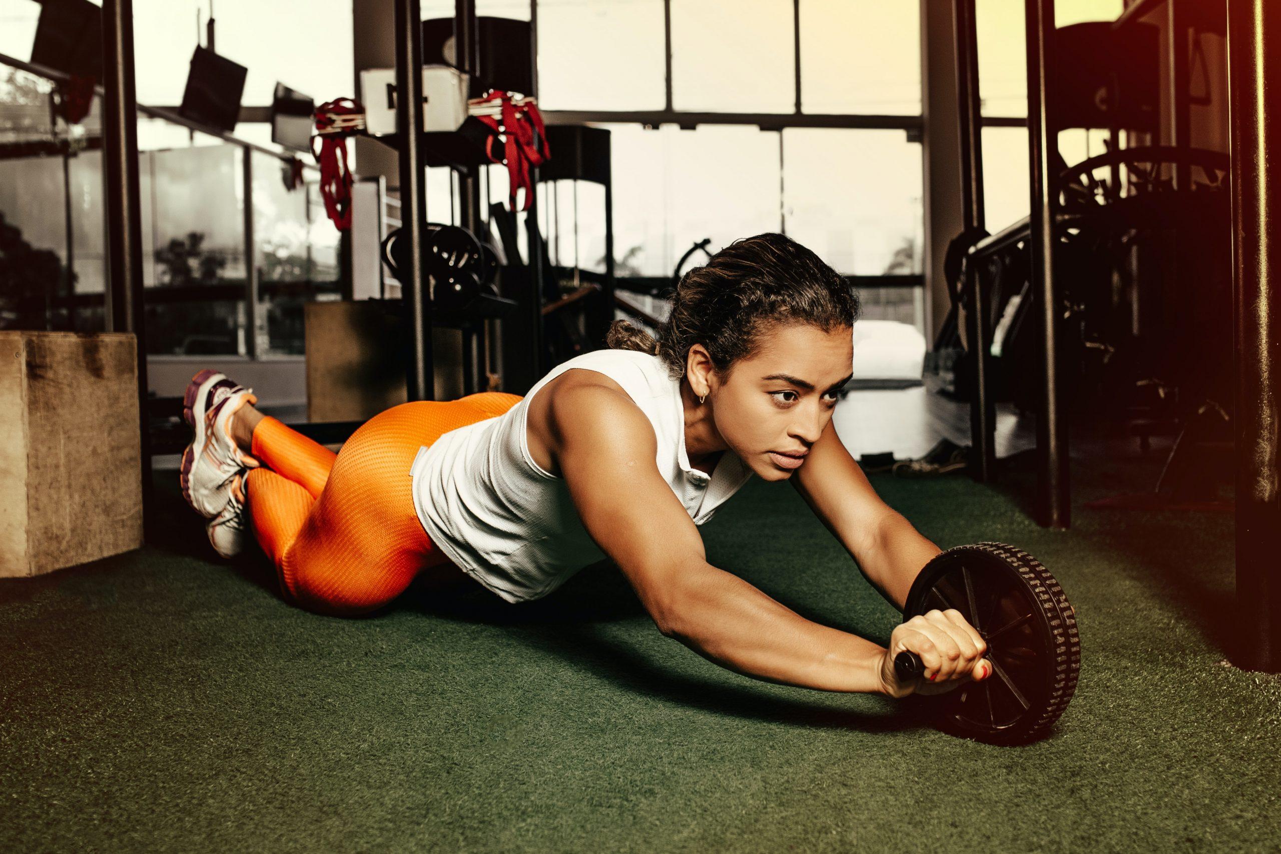 Imagem de uma mulher se exercitando com um rolinho abdominal.