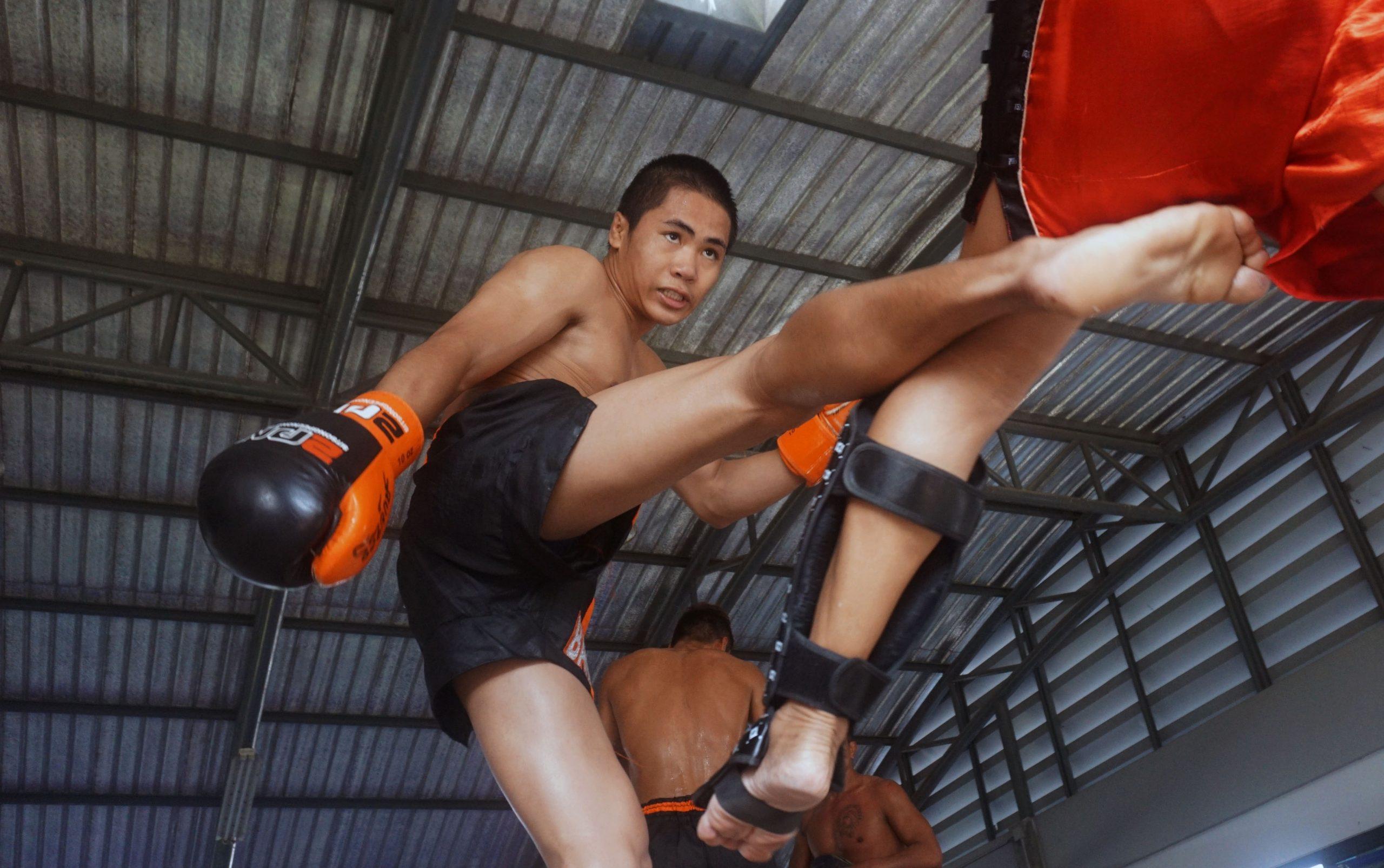 Imagem de dois rapazes lutando muay thai.