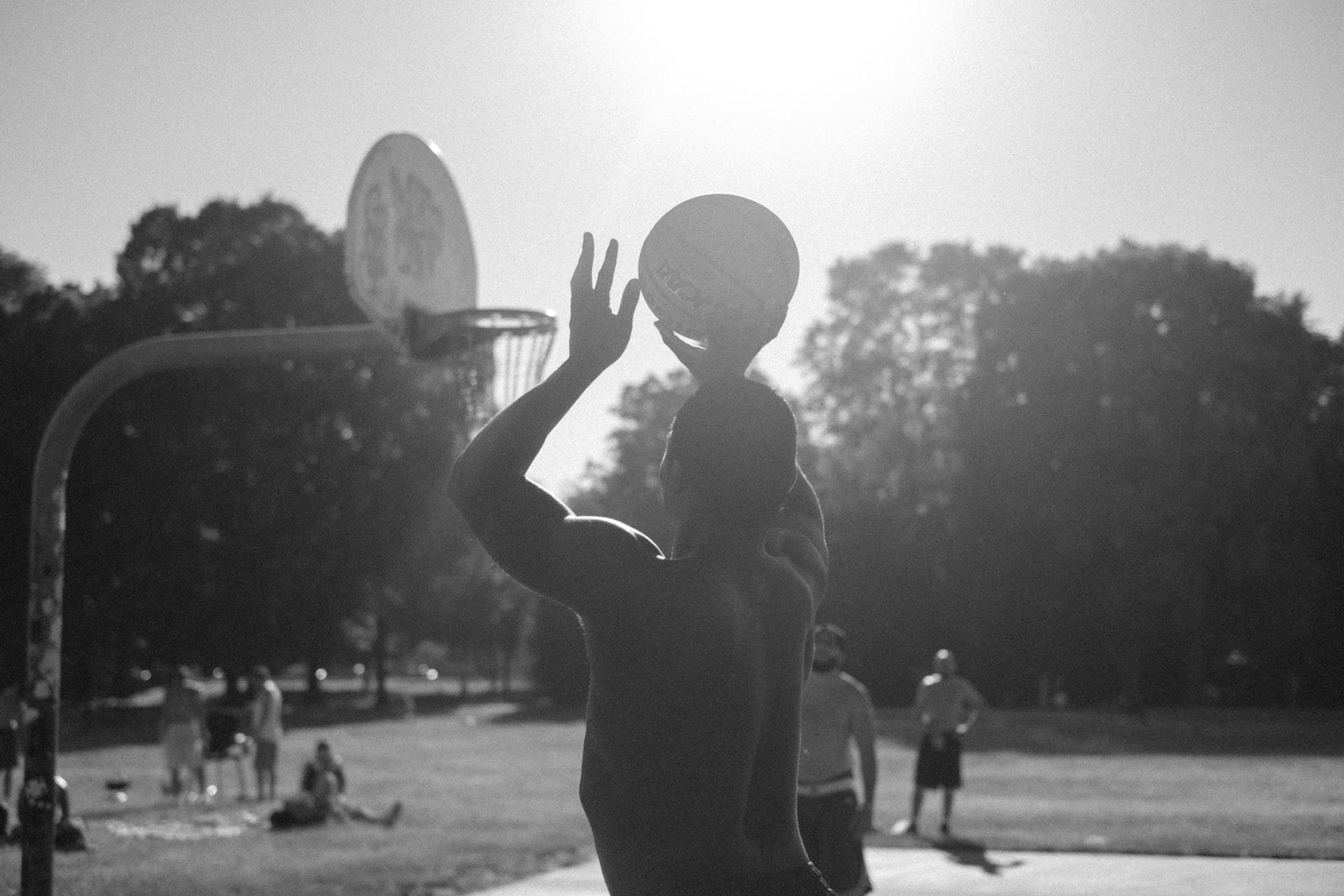 Foto em preto e branco com um homem jogando basquete ao ar livre