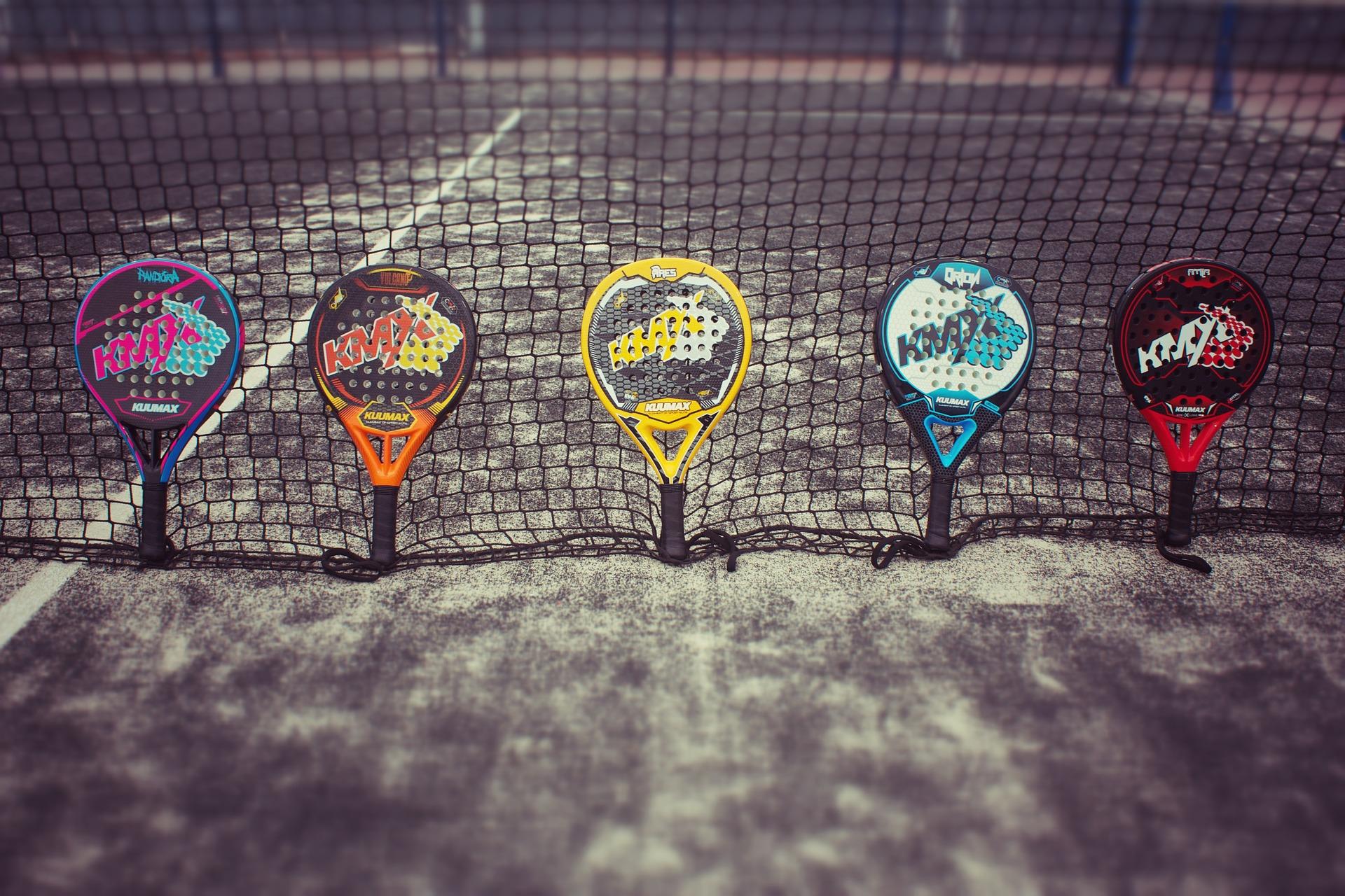 Cinco raquetes de padel colocadas em pé, lado a lado, em uma rede da quadra