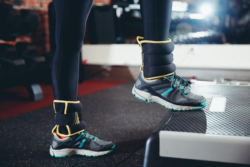 Imagem de uma mulher se exercitando com caneleiras.