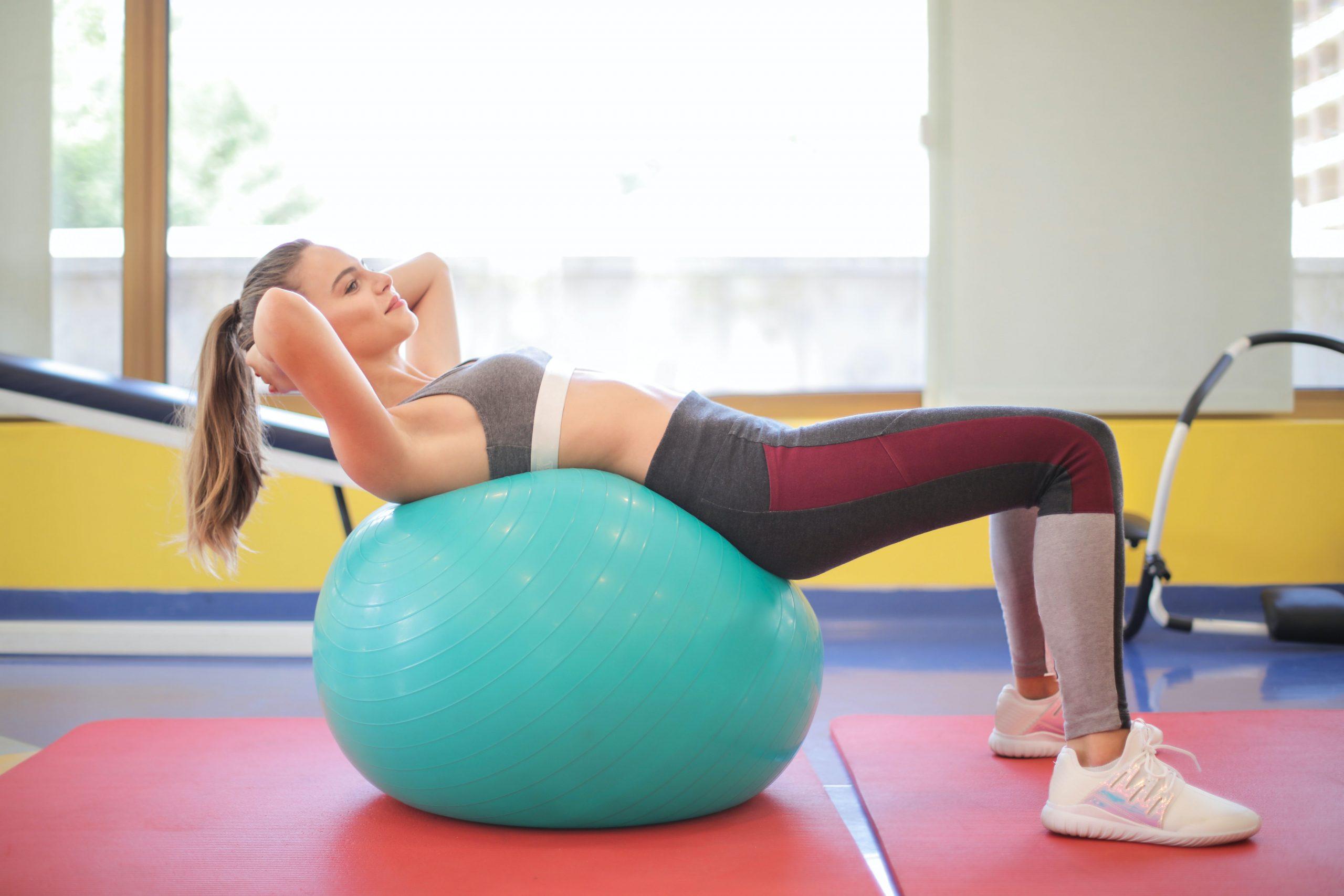 Imagem de uma mulher fazendo abdominal.
