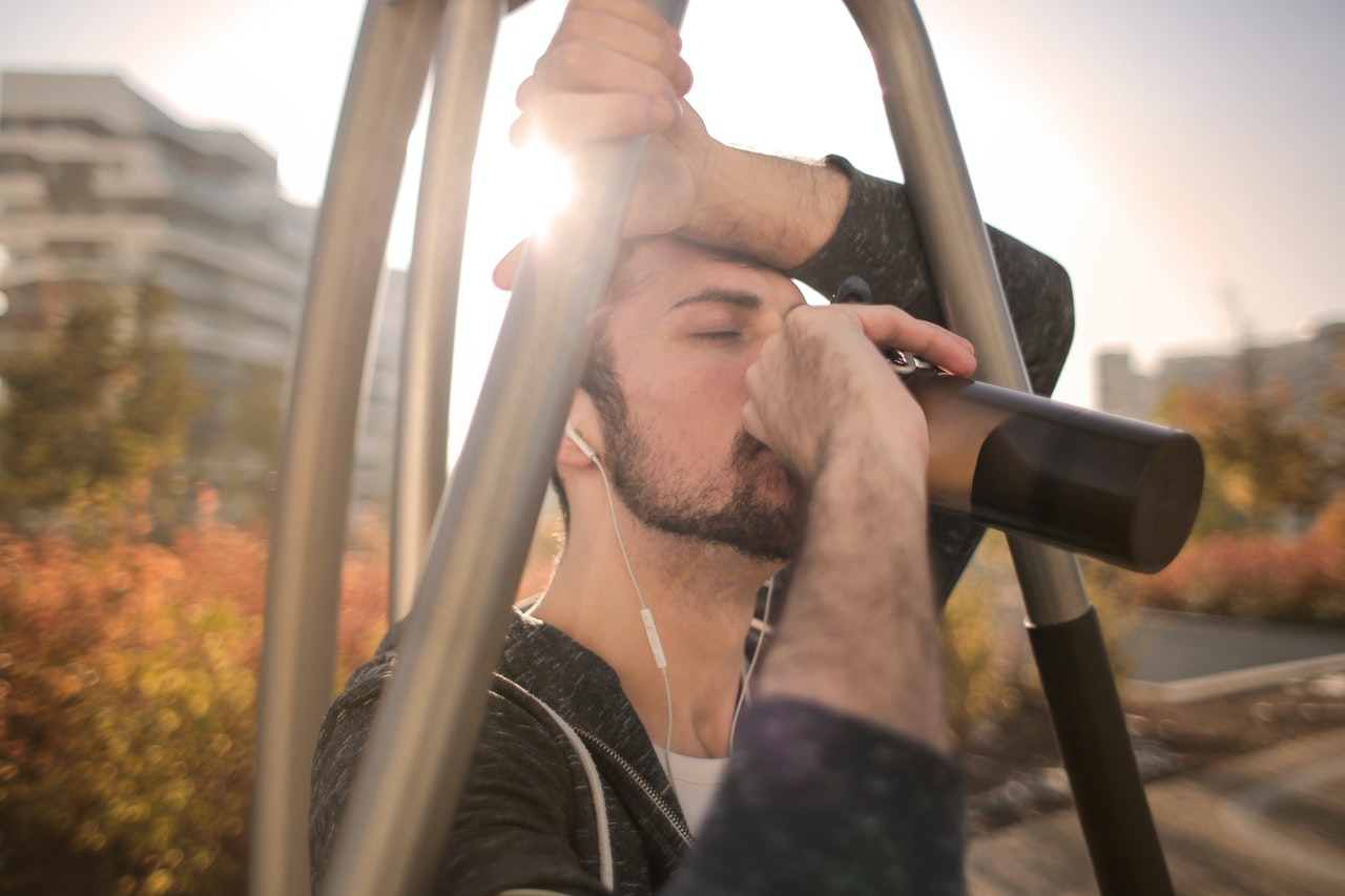 Imagem de um homem bebendo água enquanto pratica esporte.
