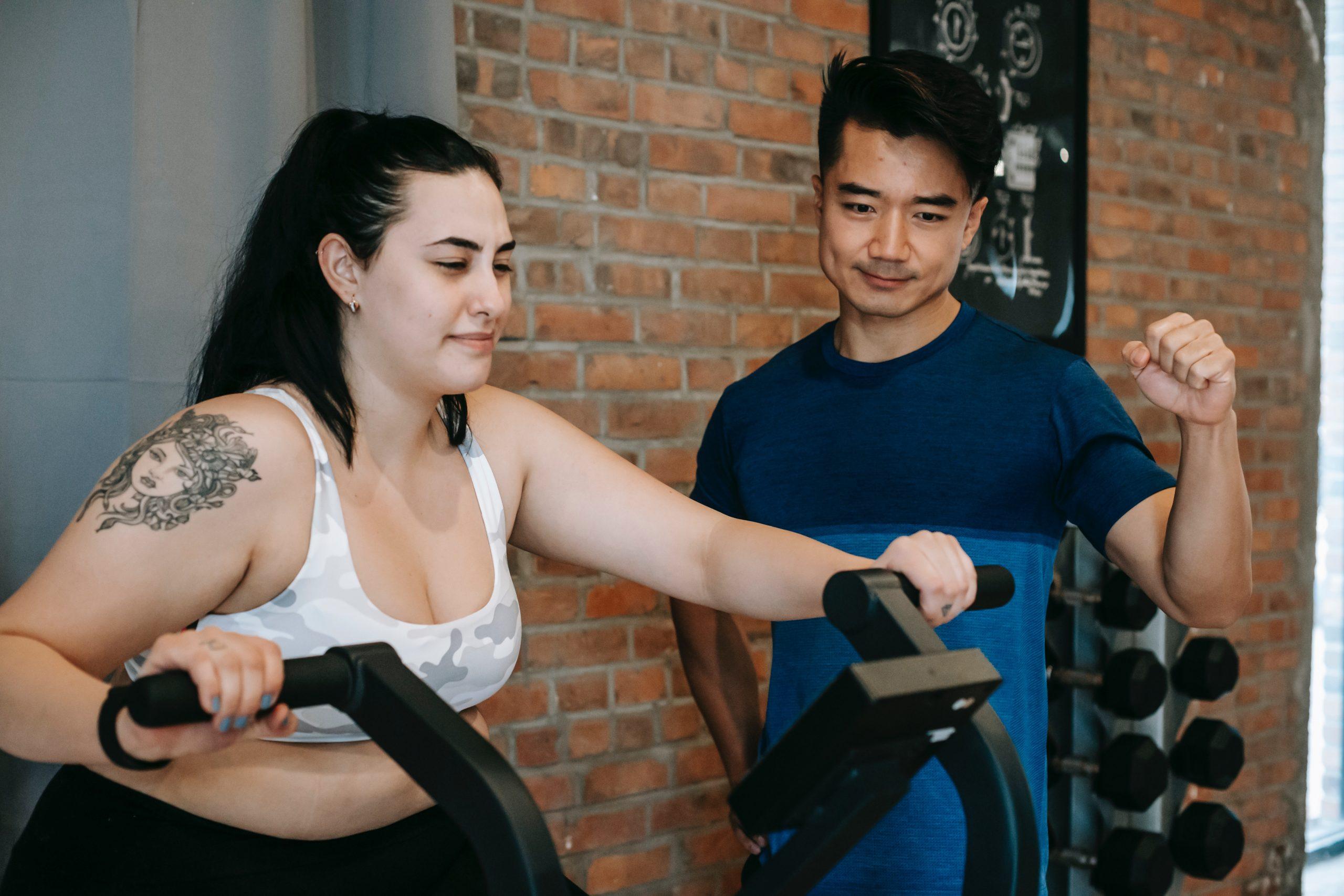 Imagem de uma mulher treinando junto ao seu personal trainer.