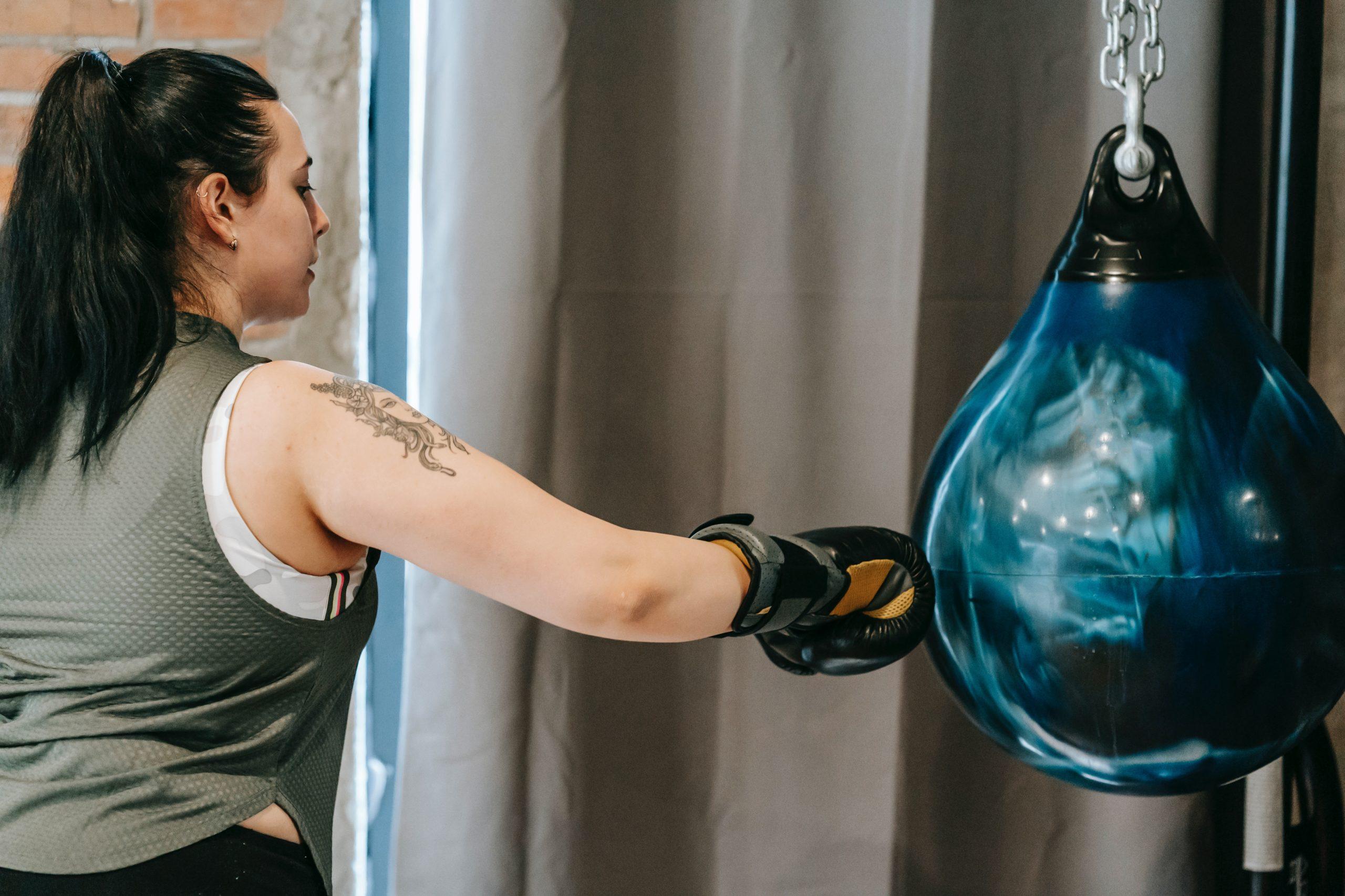 Mulher com luva de boxe tocando em um punching ball azul suspenso no teto