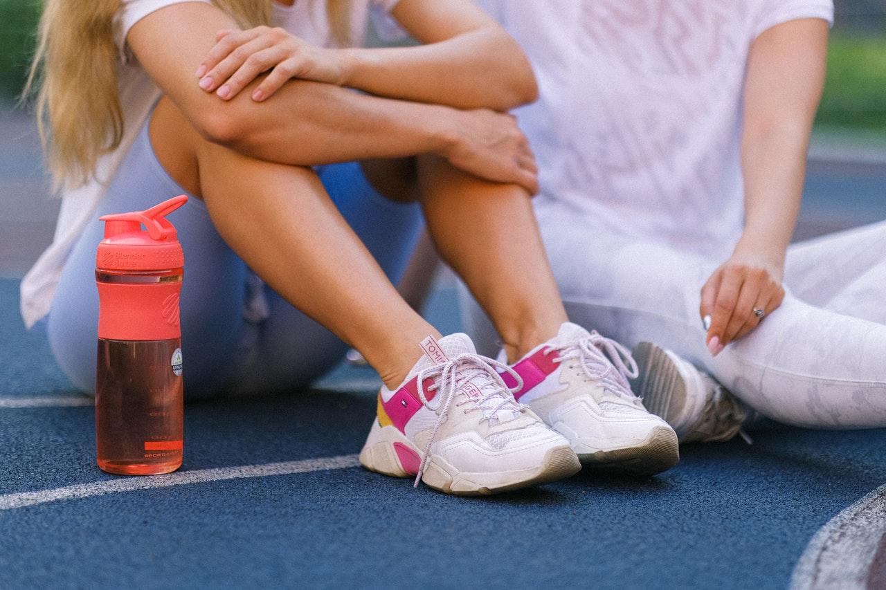 Imagem de duas mulheres sentadas sobre uma quadra esportiva.