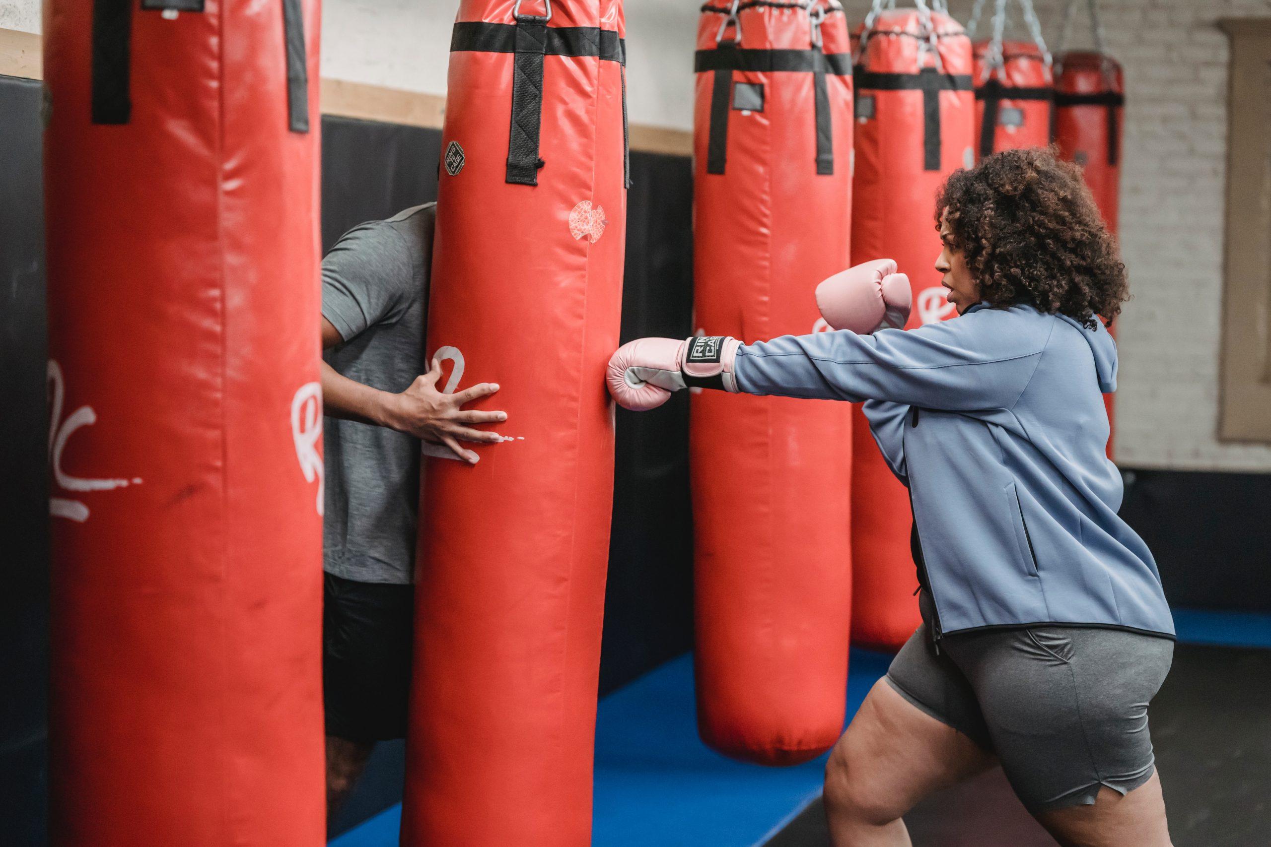 Mulher em uma academia fazendo golpe em um saco de pancada sendo acompanhada pelo professor