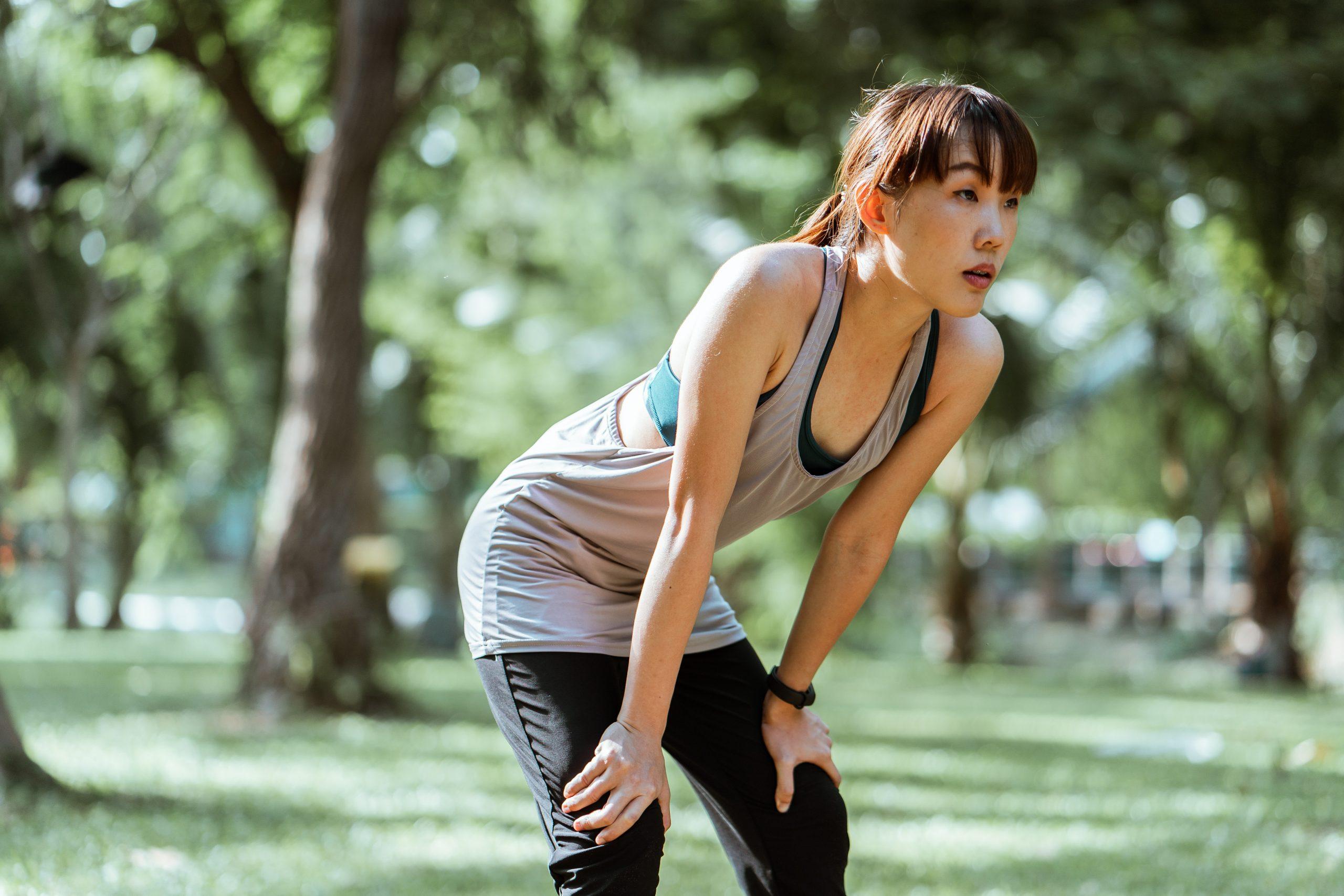Imagem de uma mulher demonstrando cansaço enquanto se exercita.