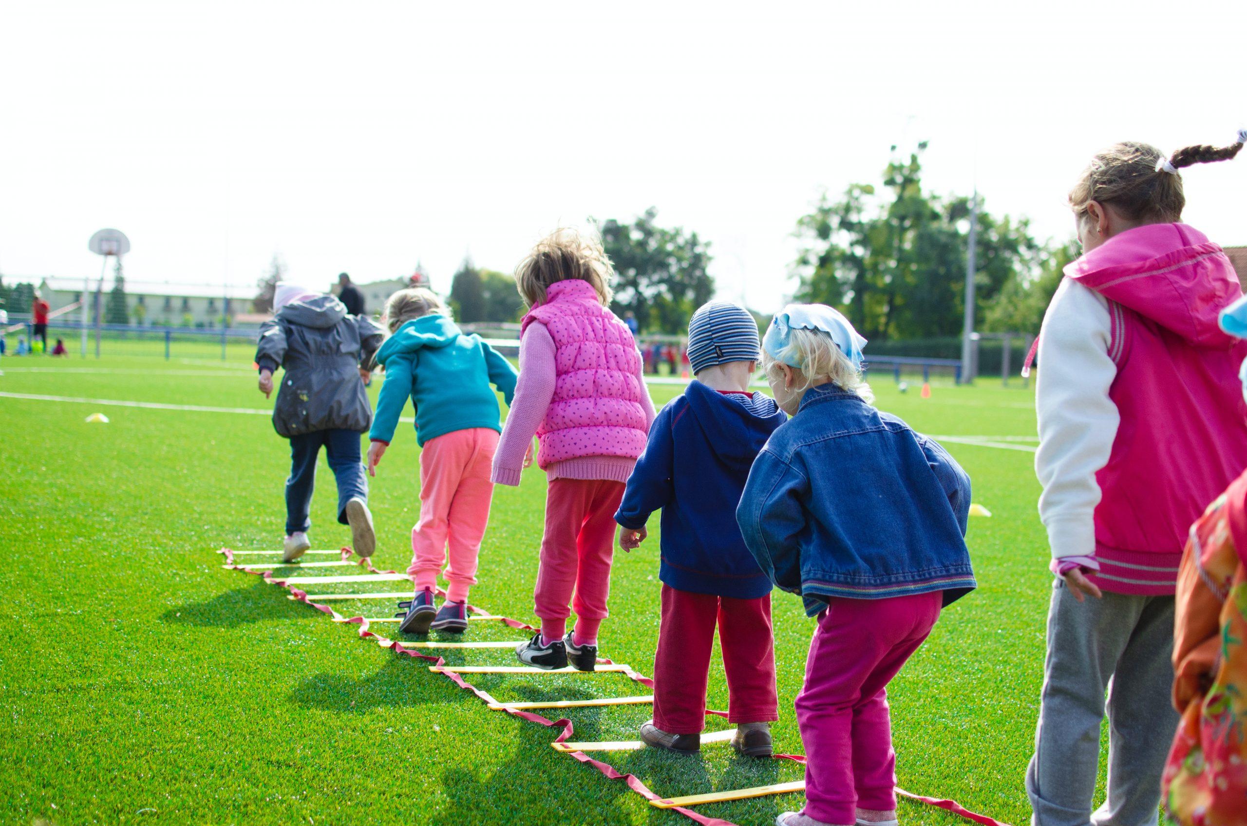 Imagem de crianças praticando esporte em uma escada de agilidade.