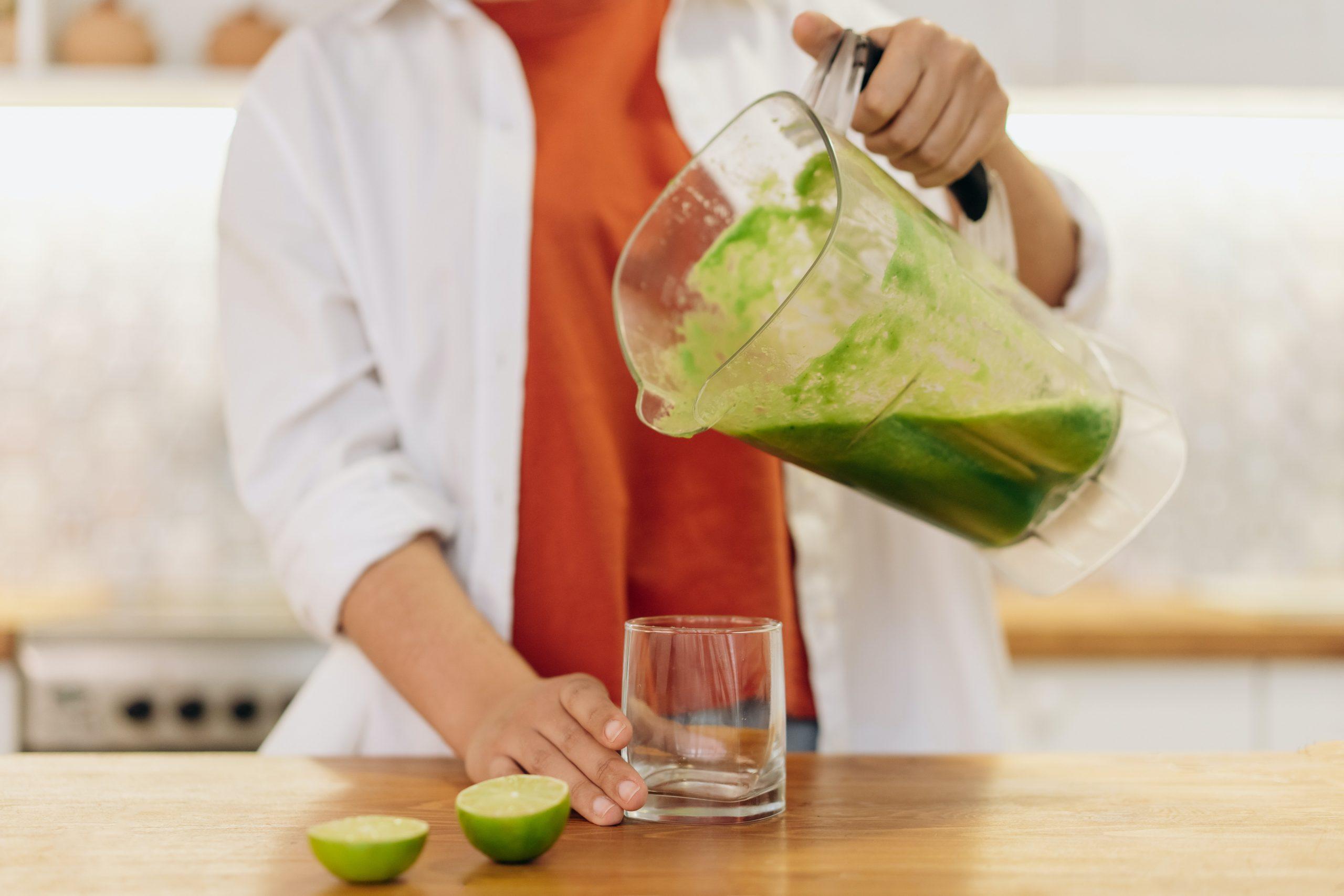 Imagem de uma mulher preparando suco verde.