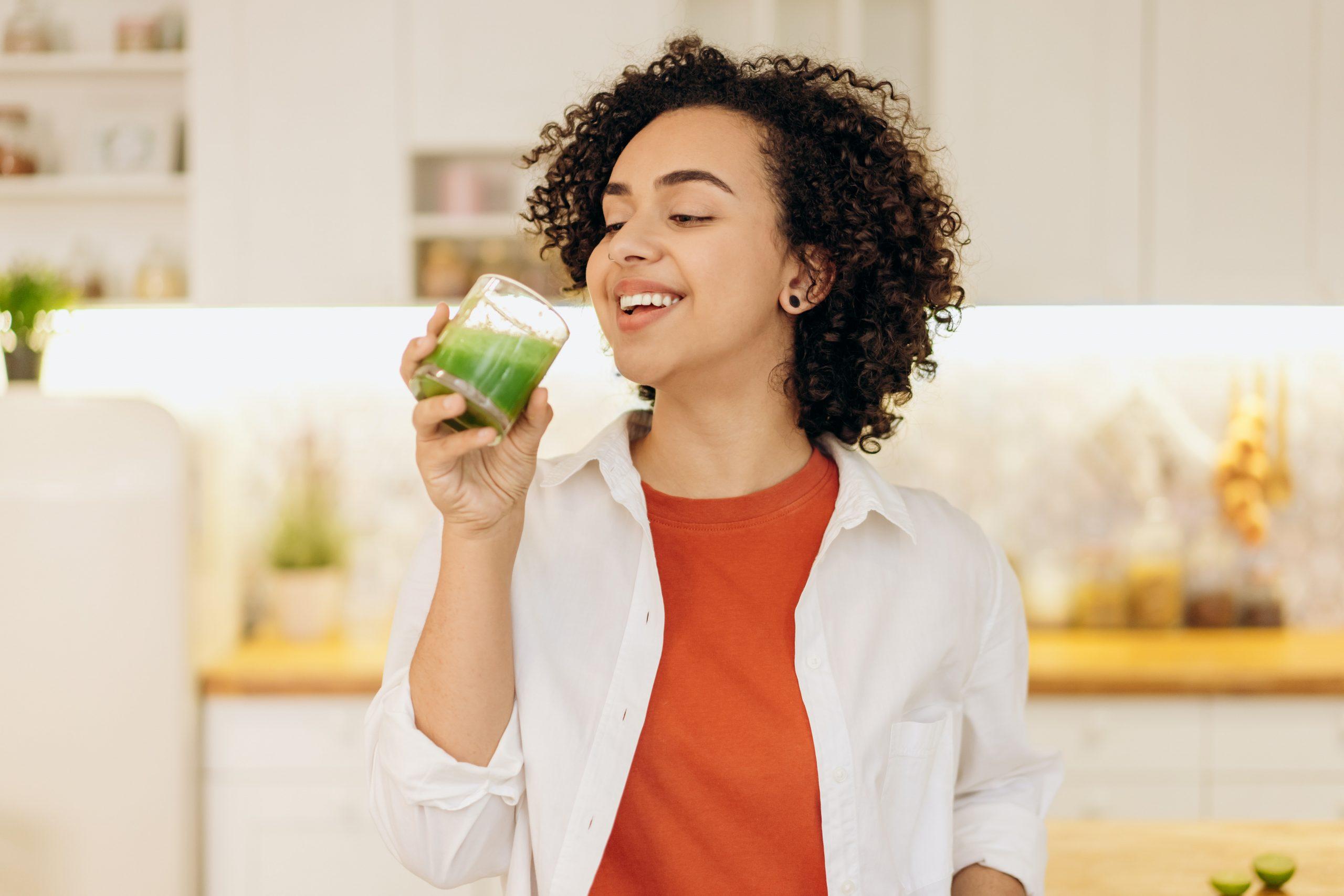 Imagem de uma mulher tomando suco verde.