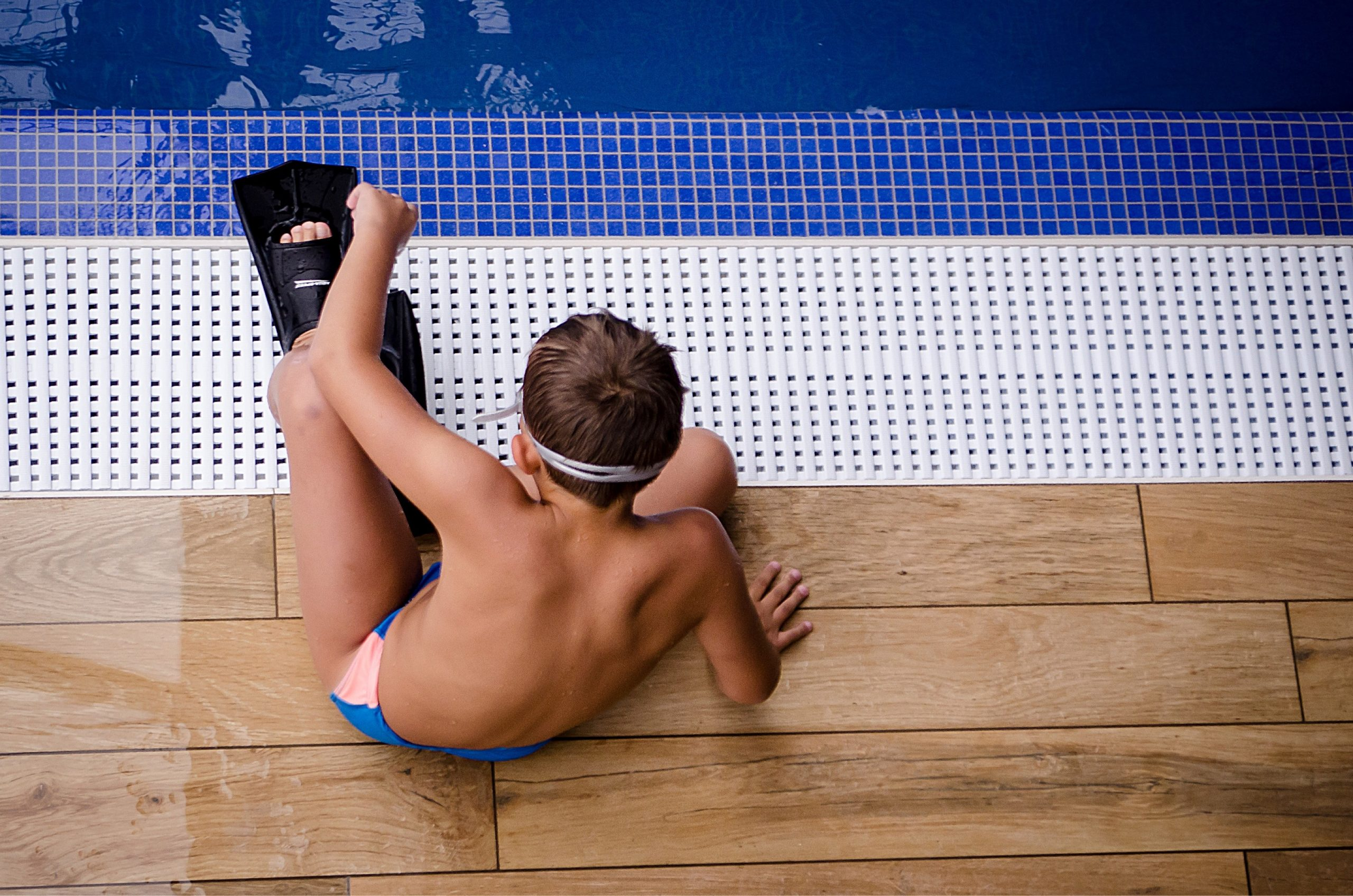 Menino sentado na beirada da piscina com roupa de natação e pés de pato