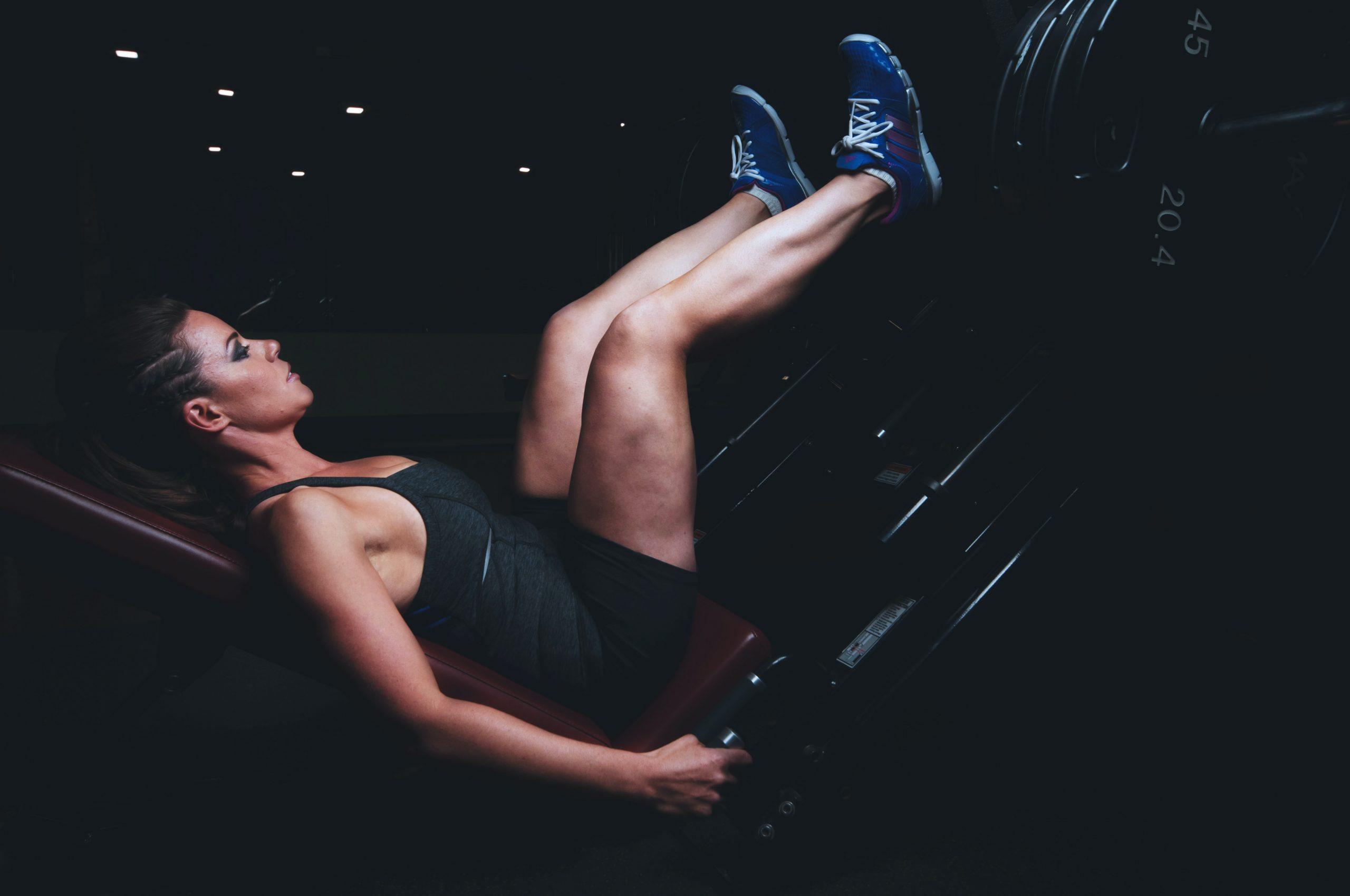 Imagem de uma mulher fazendo leg press.