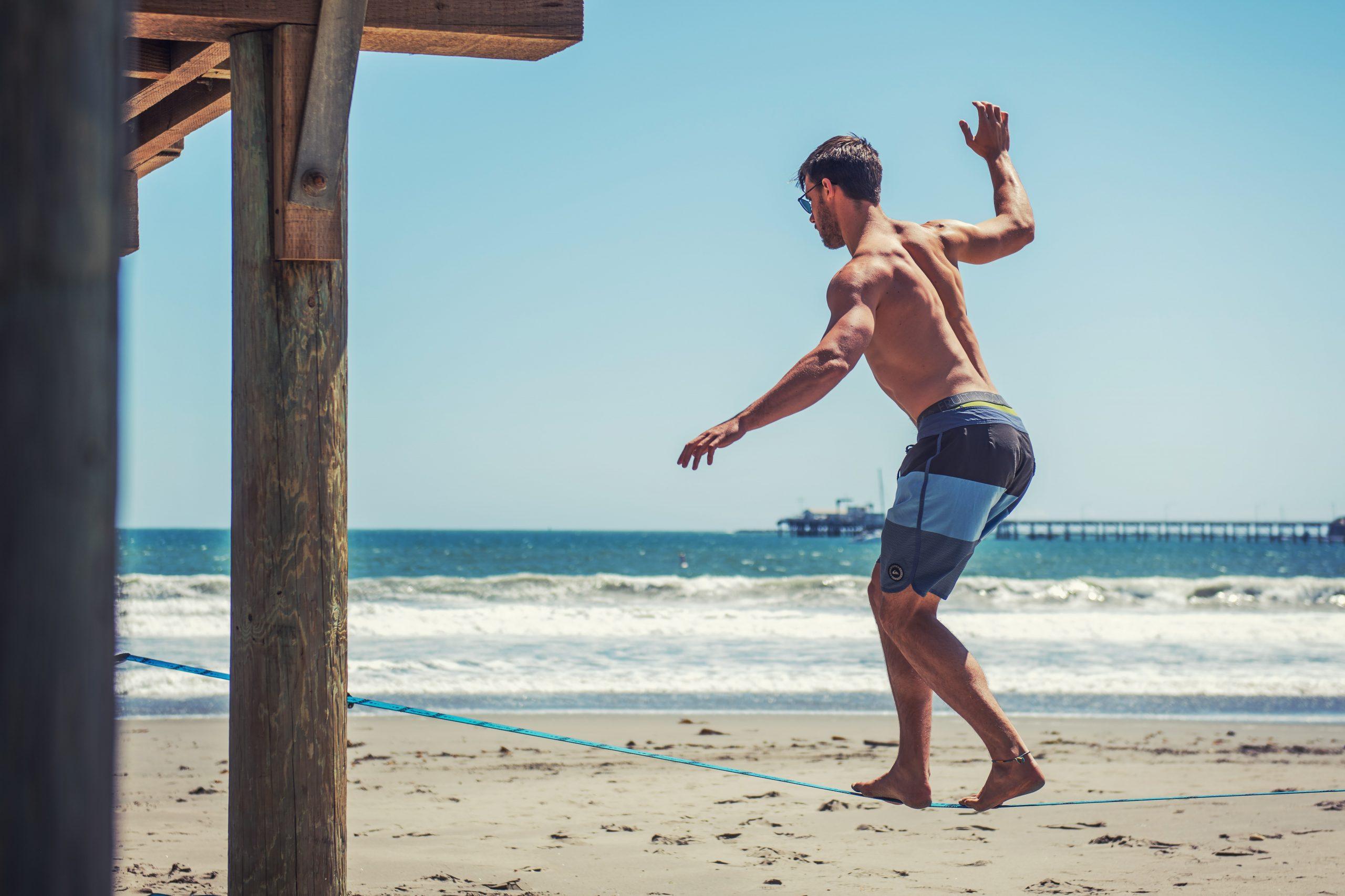 Homem praticando slackline na praia.