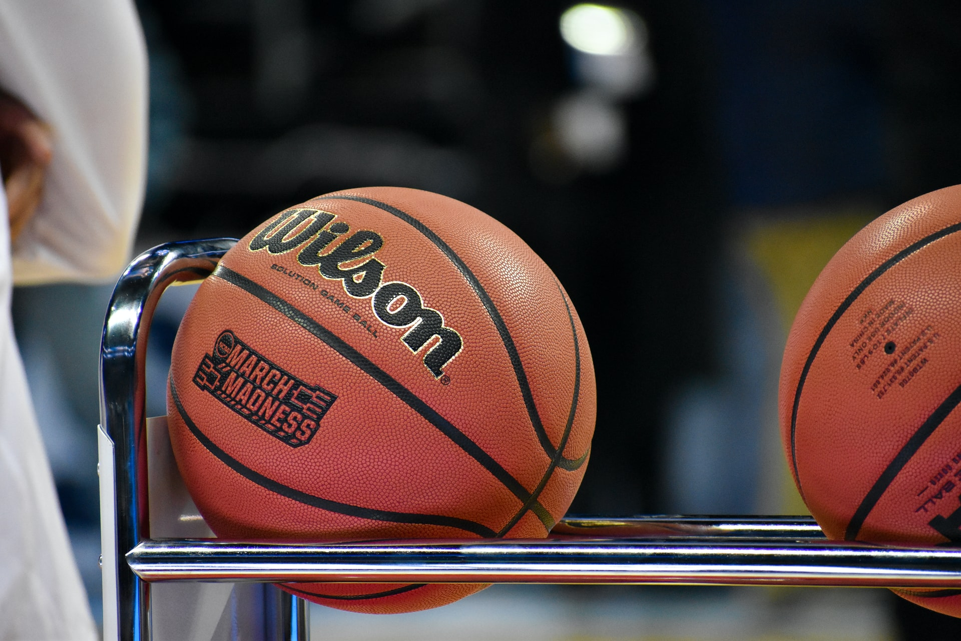Foto em close de uma bola de basquete da Wilson. Ela está em cima de um suporte para bolas