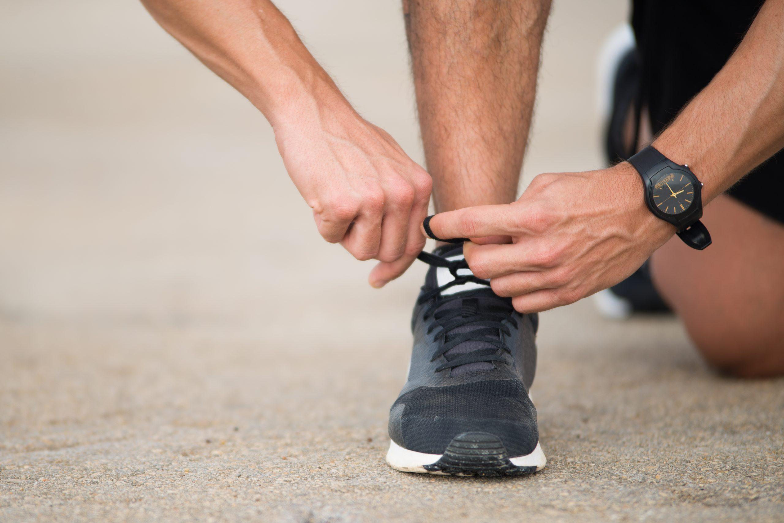 Tênis preto sendo amarrado por homem que vai correr.