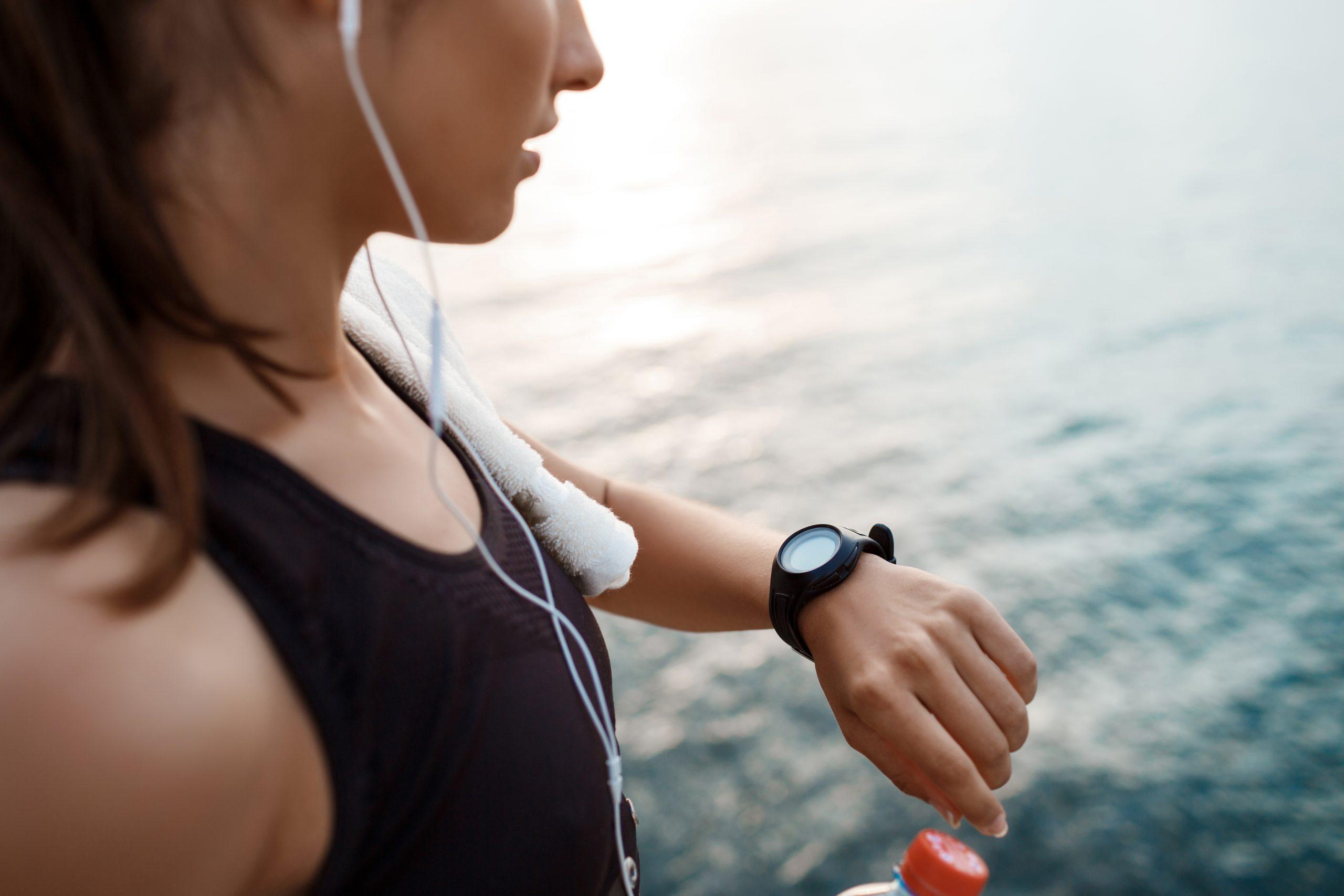 Mulher com roupa de academia olhando em um monitor cardíaco