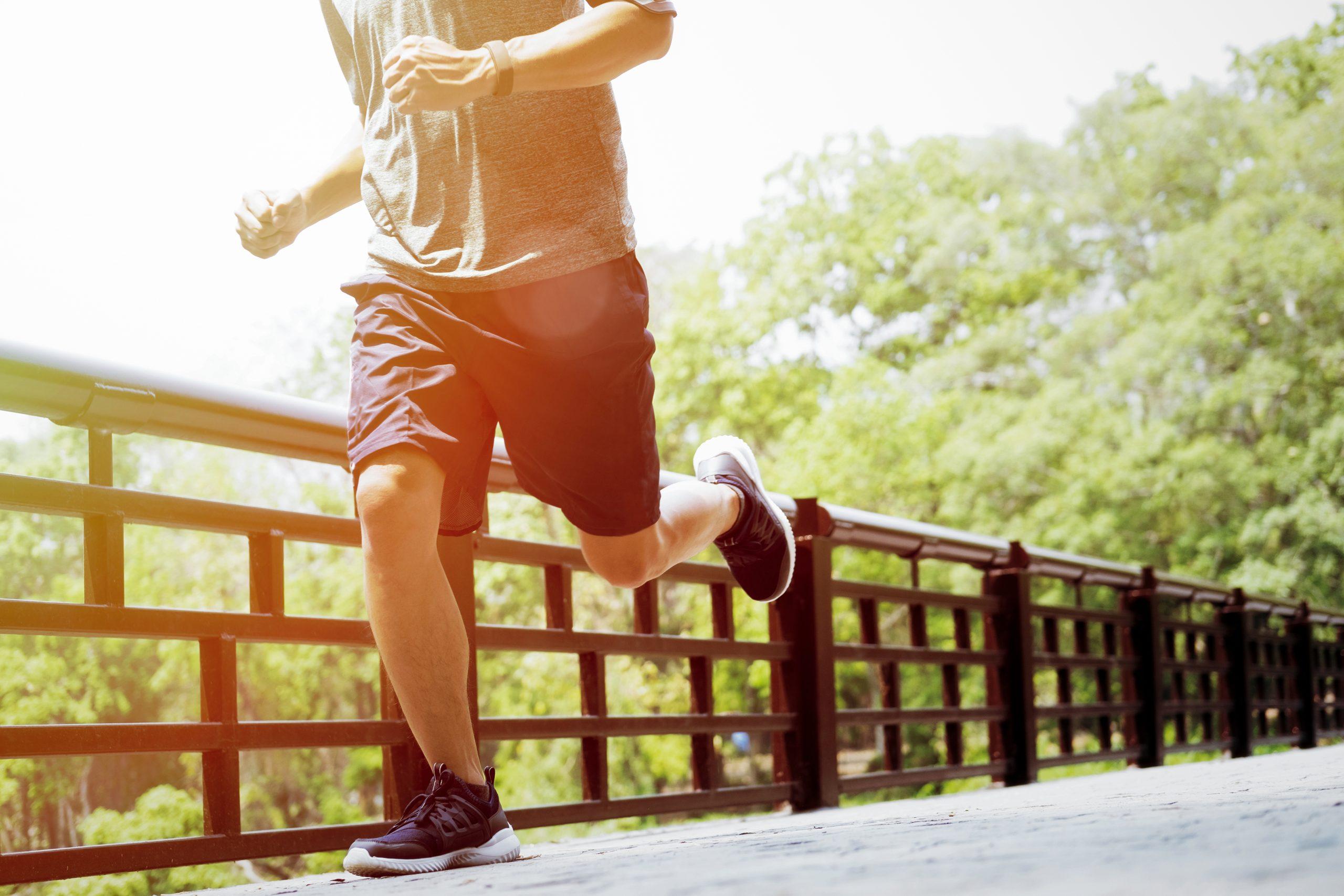 Homem de costas correndo na rua.