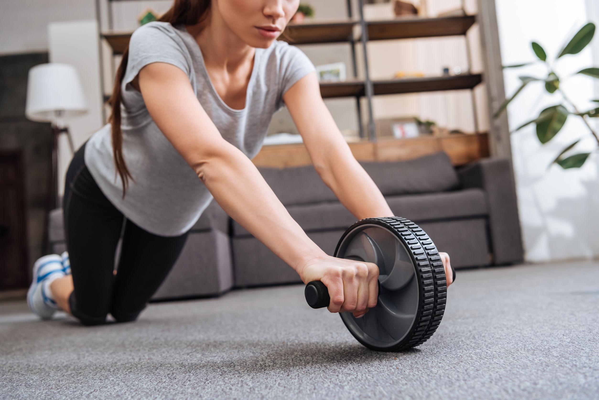 Foto de uma mulher em uma academia realizando um exercício para abdominais com uma roda abdominal