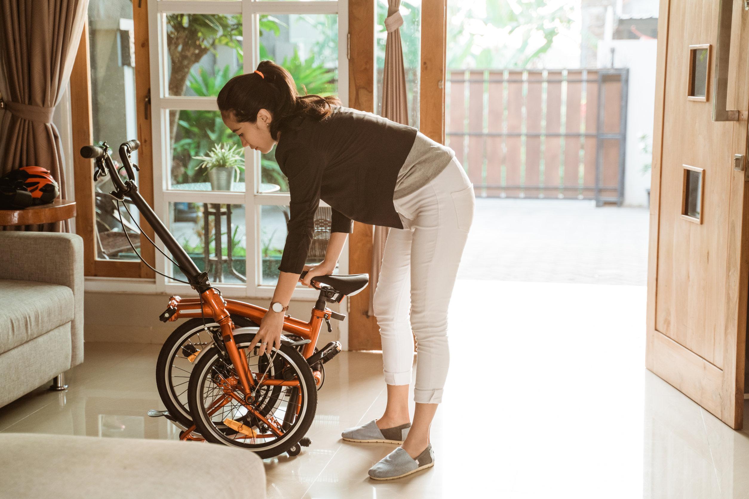 Foto de uma mulher na sala de casa guardando a sua bicicleta dobrável