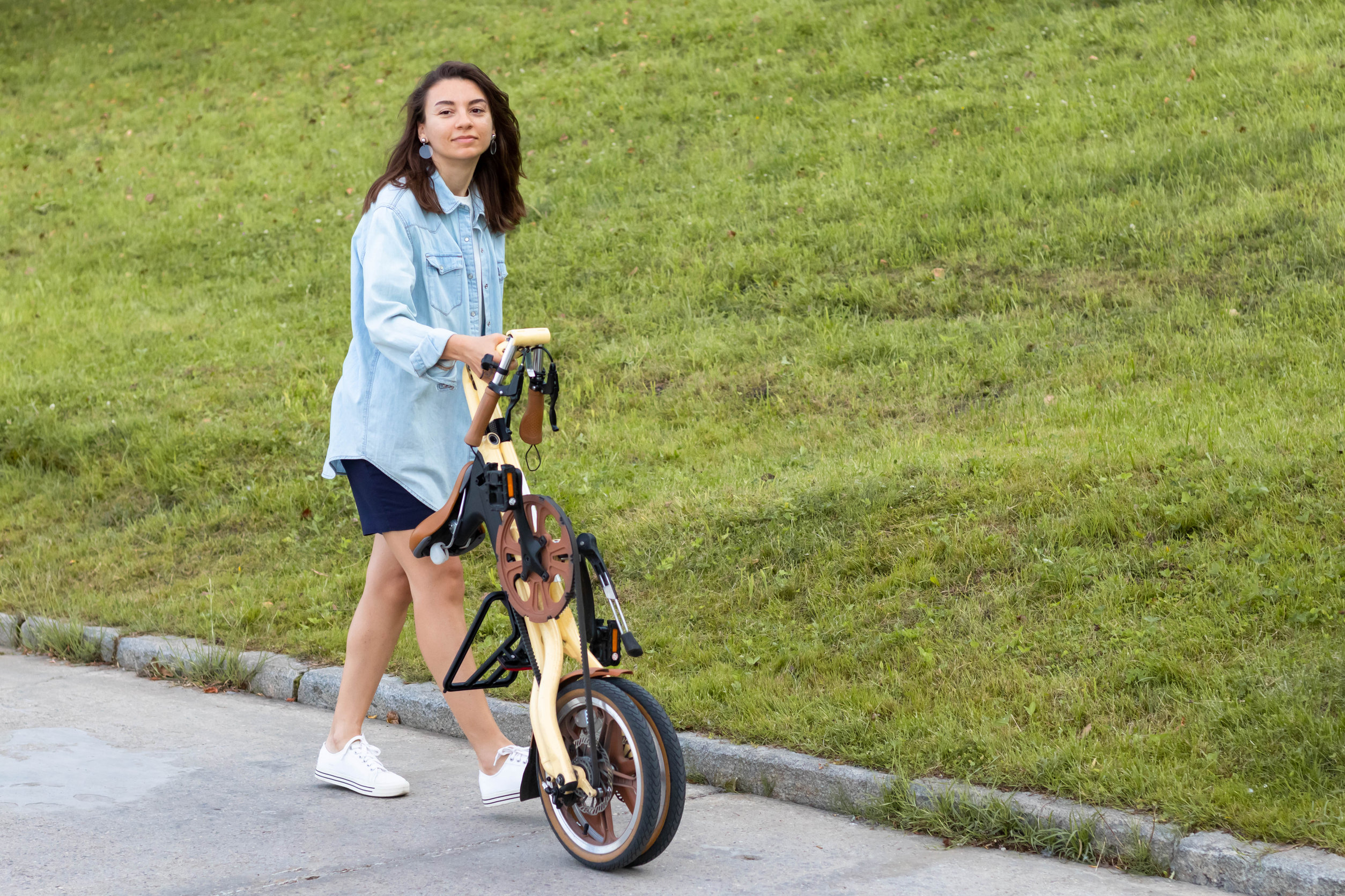Foto de uma mulher empurrando uma bicicleta dobrada