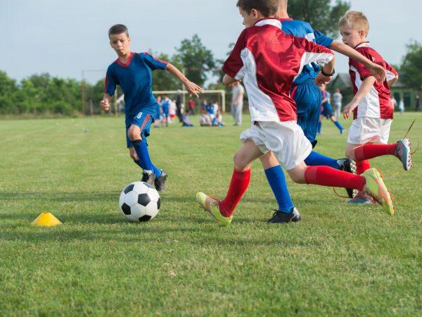 30683290 – boys kicking football on the sports field