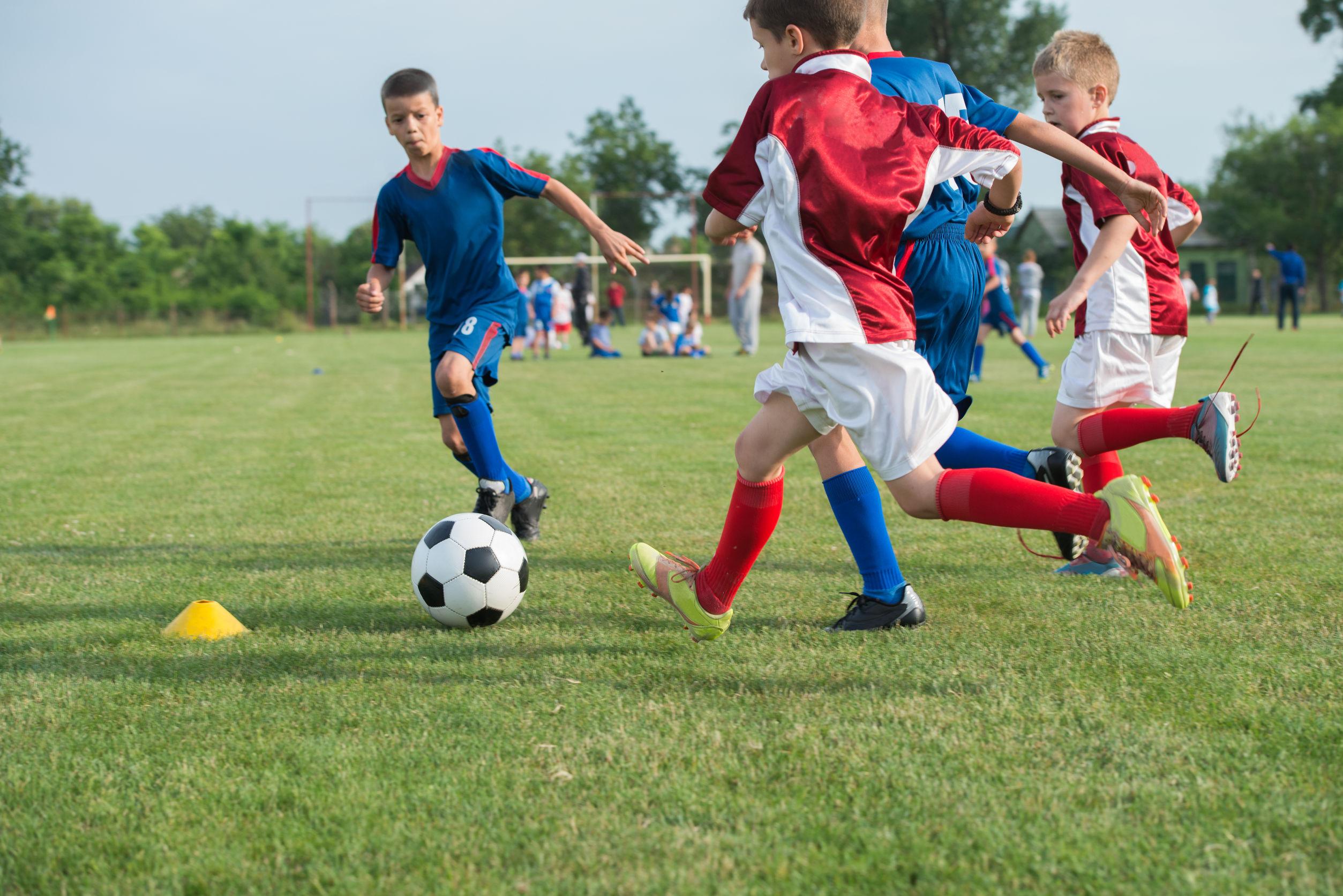 Foto de crianças jogando futebol de campo