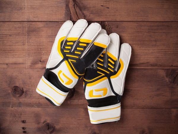 Gloves of the soccer goalkeeper on wooden table