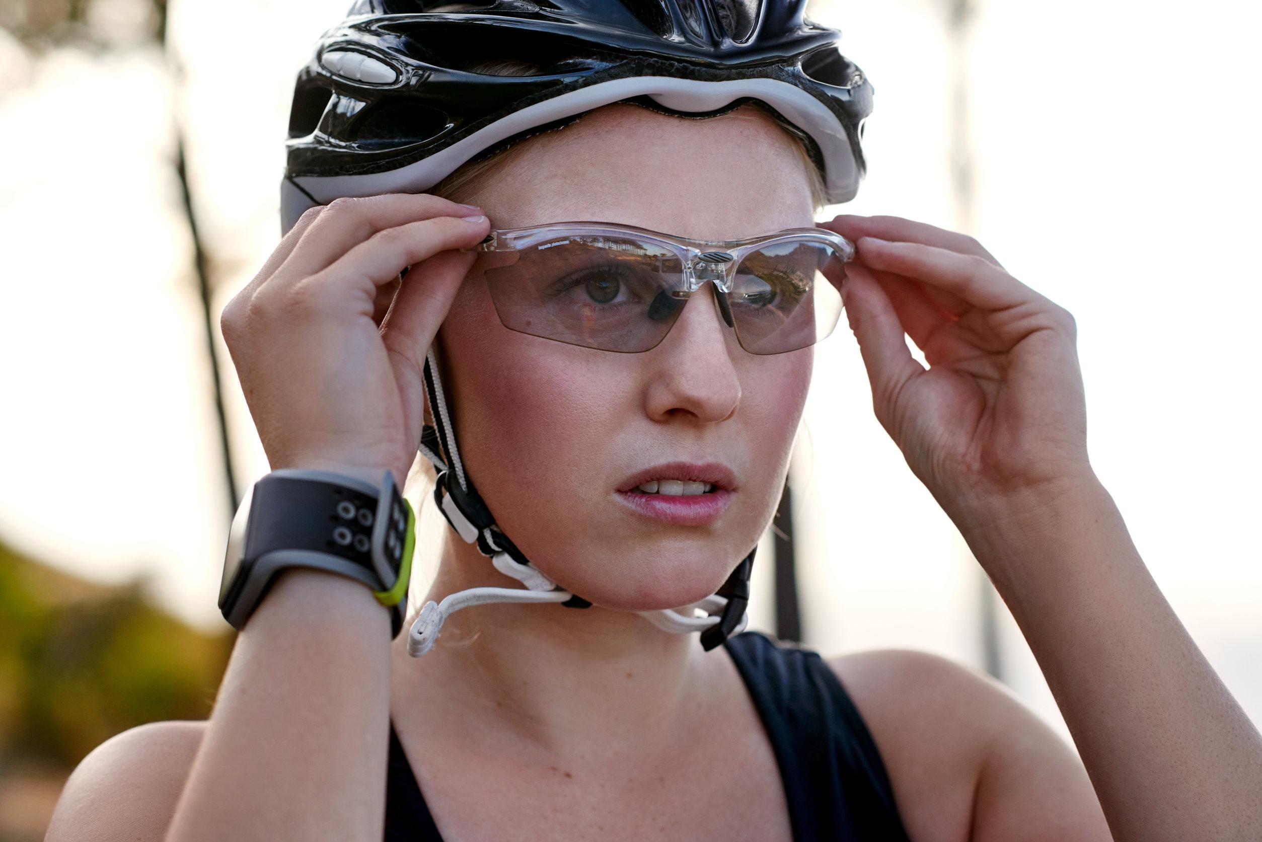 A foto mostra uma ciclista colocando os óculos de ciclismo com as duas mãos