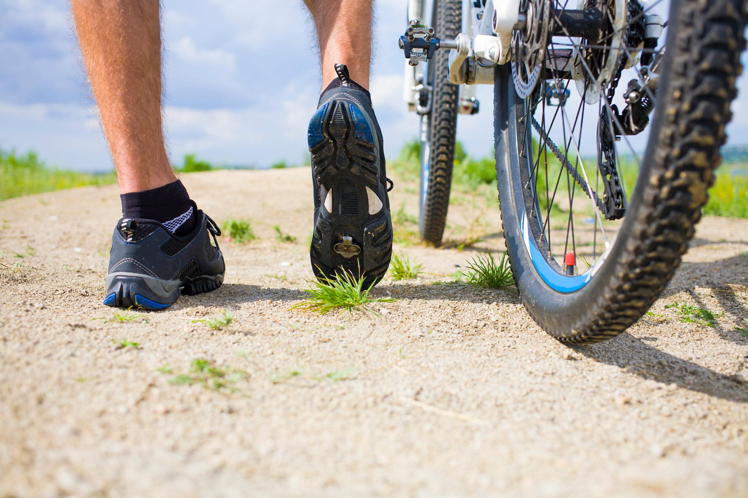 Pés de um homem com sapatilhas de ciclismo ao lado de uma bicicleta em um solo montanhoso