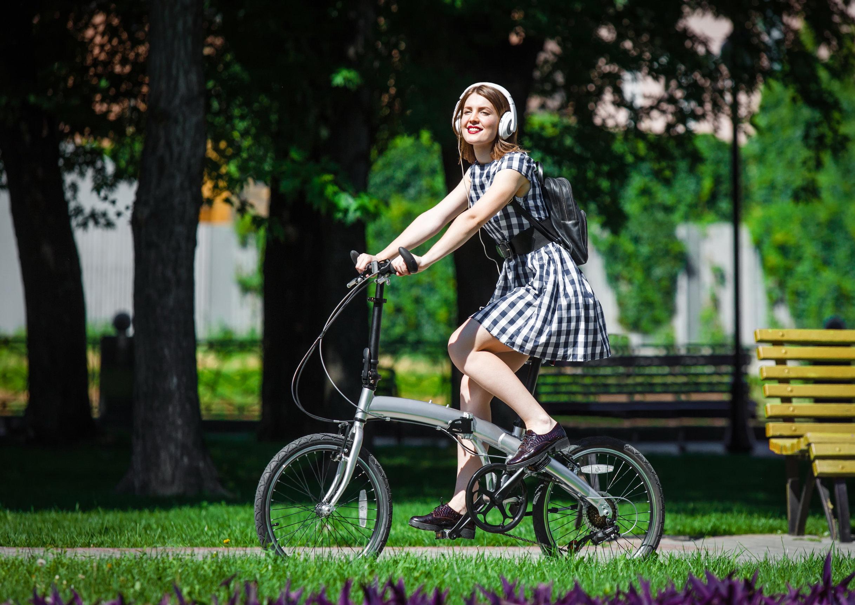 Foto de uma estudante pedalando em um parque com uma bicicleta dobrável