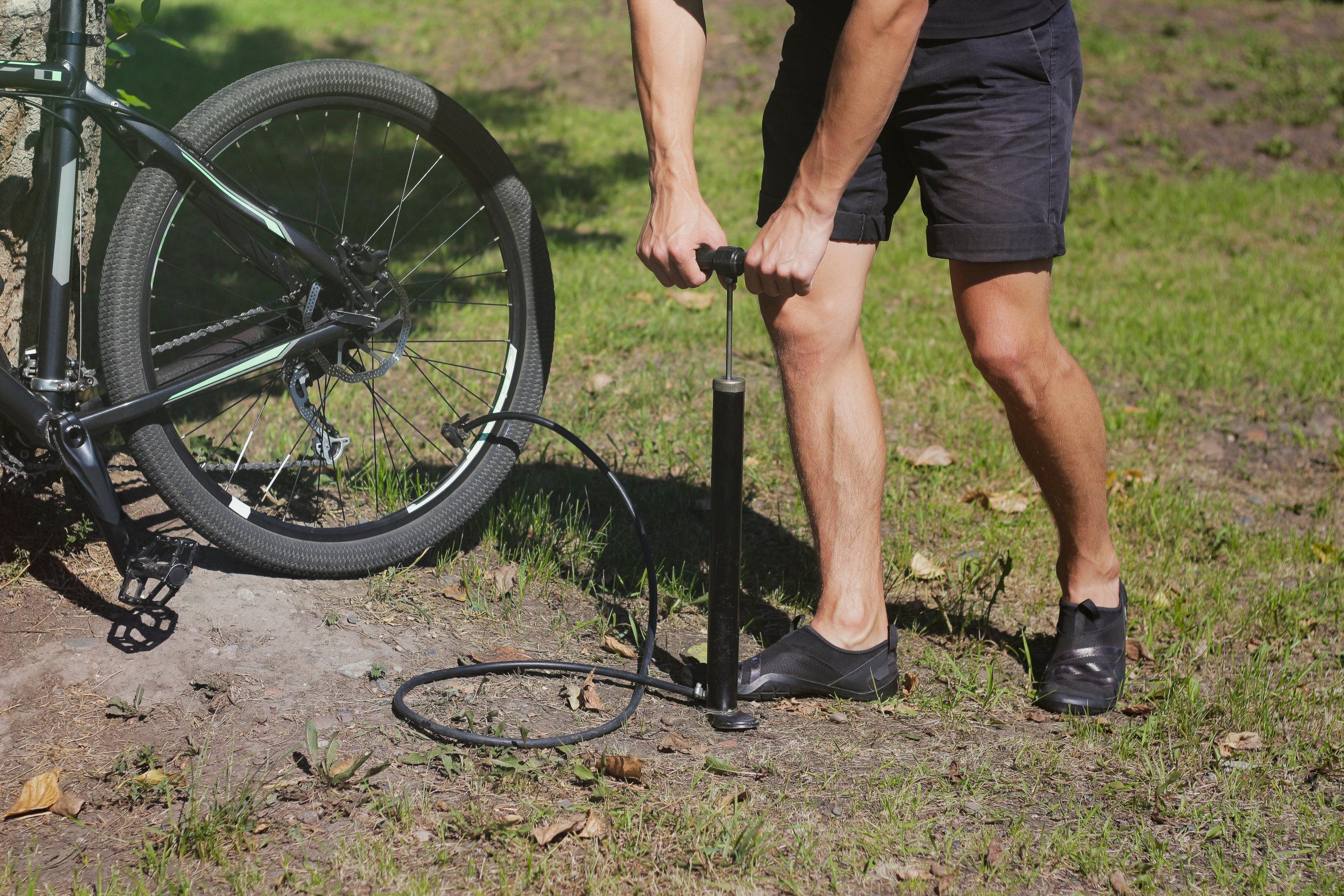 Ciclista enchendo pneu da bicicleta com uma bomba de bicicleta