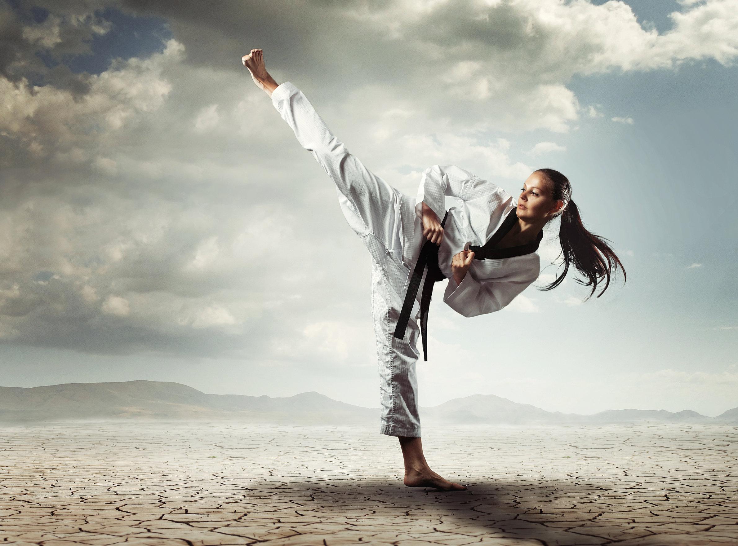 A foto mostra uma atleta de karatê praticando um chute para cima
