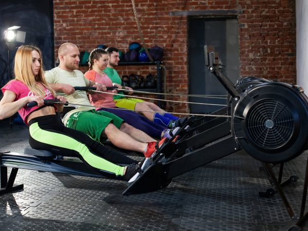 The group of young people is doing workout on the rowing machines at the gym