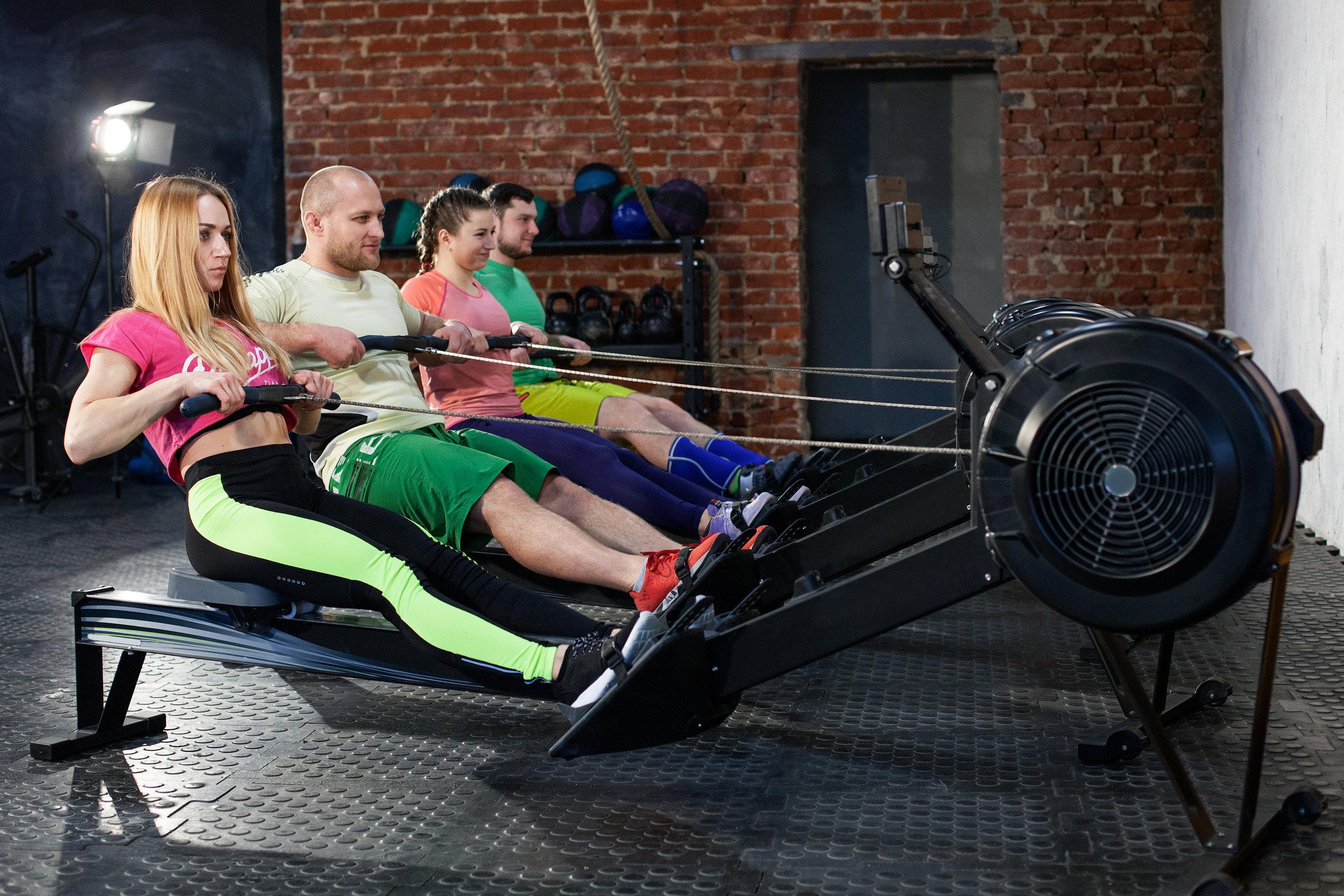 Grupo de pessoas na academia fazendo exercício físico no simulador de remo