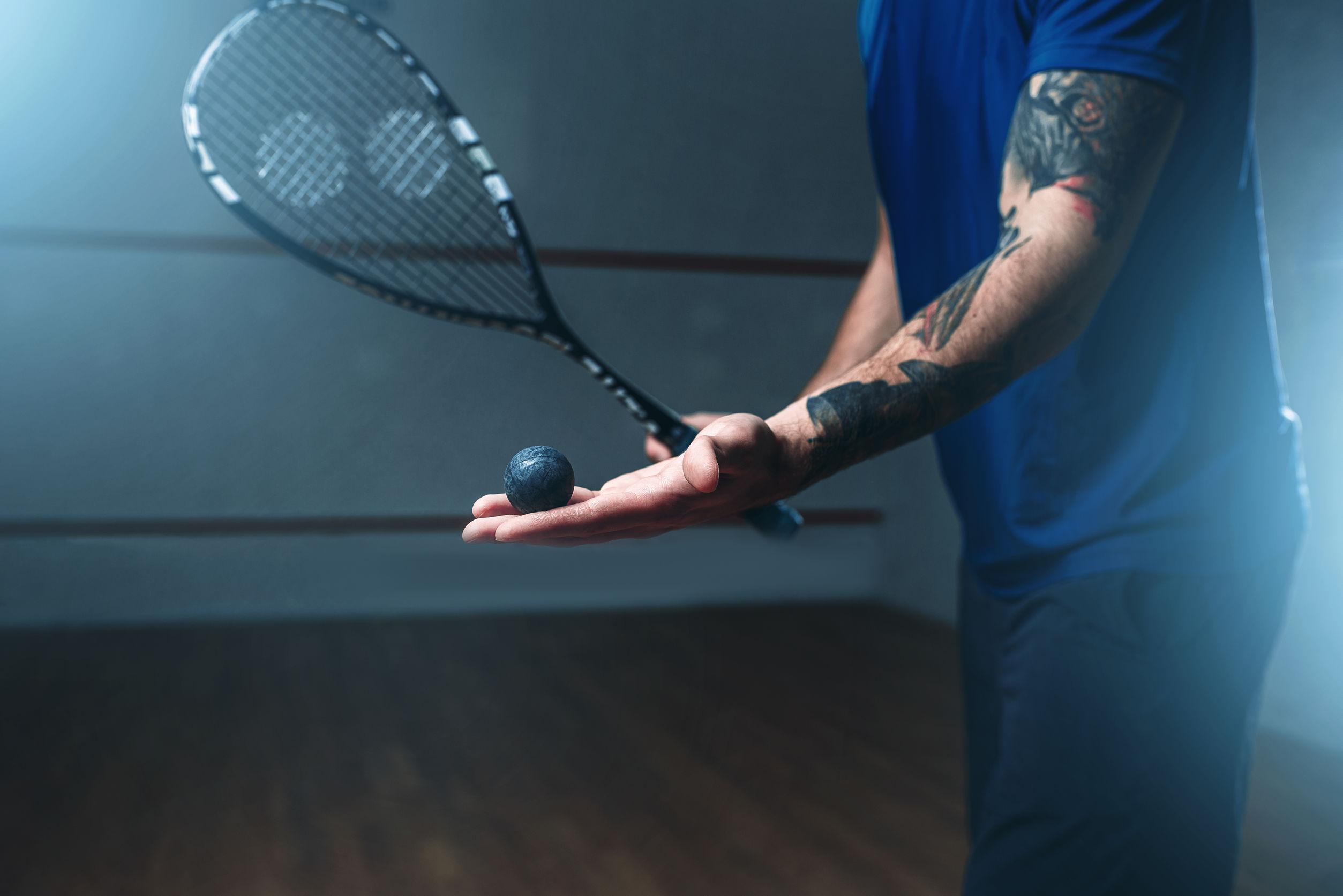 Foto em que aparece metade do braço de um homem segurando uma bolinha de squash em uma mão, com uma raquete de Squash ao fundo