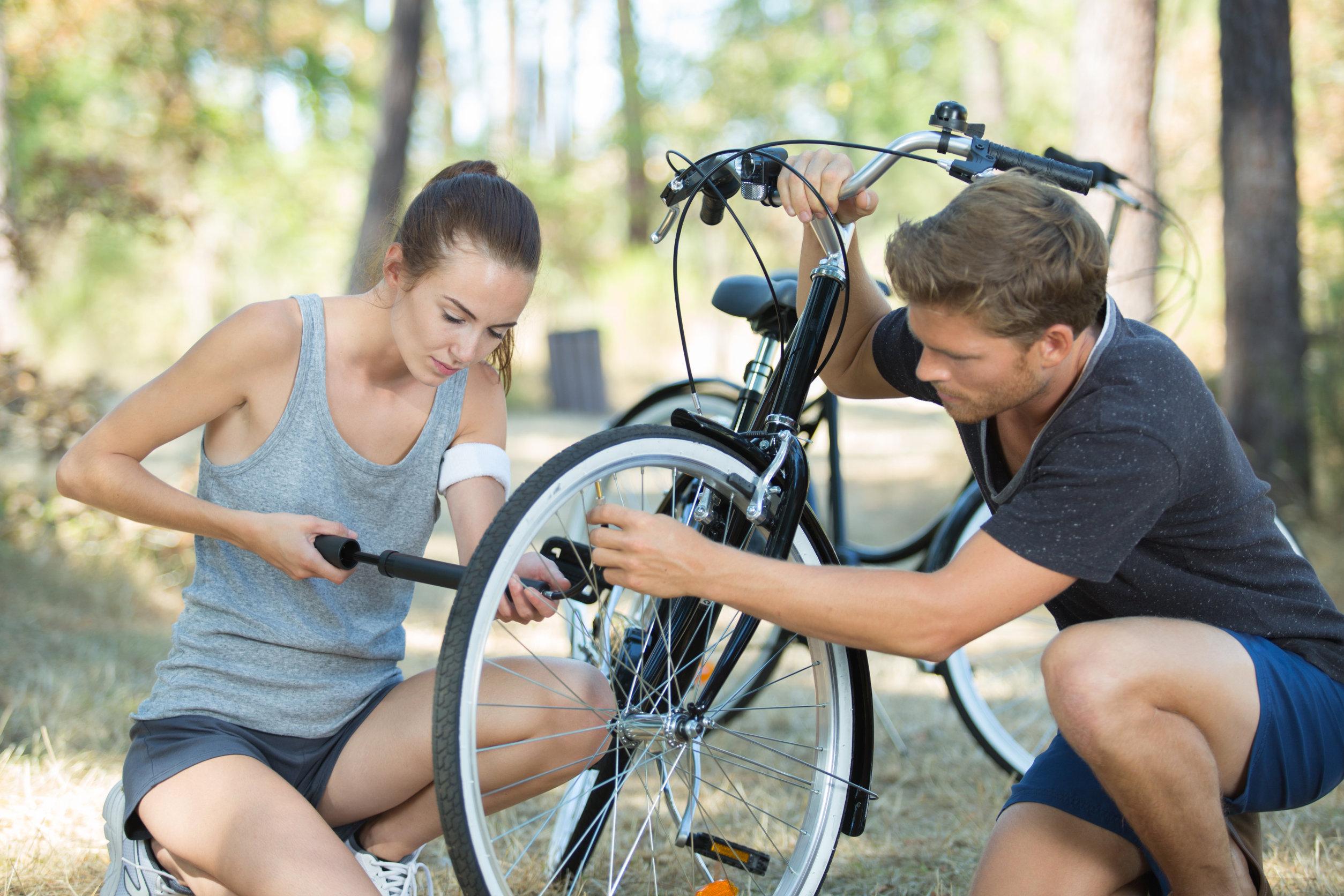 Foto de um casal enchendo o pneu de uma bicicleta