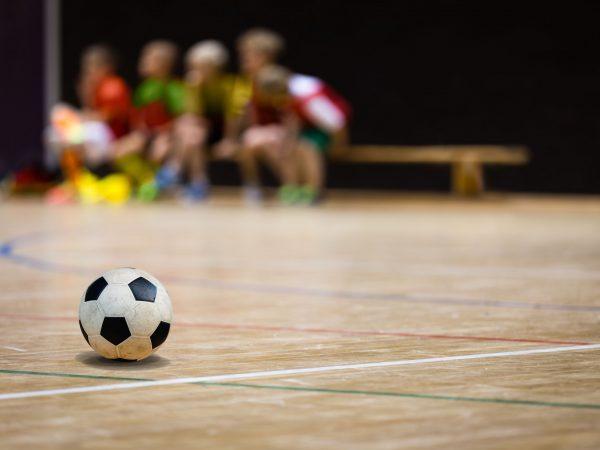 89515674 – football futsal ball and youth team. indoor soccer sports hall. children indoor soccer team. sport futsal background. indoor soccer winter league for kids