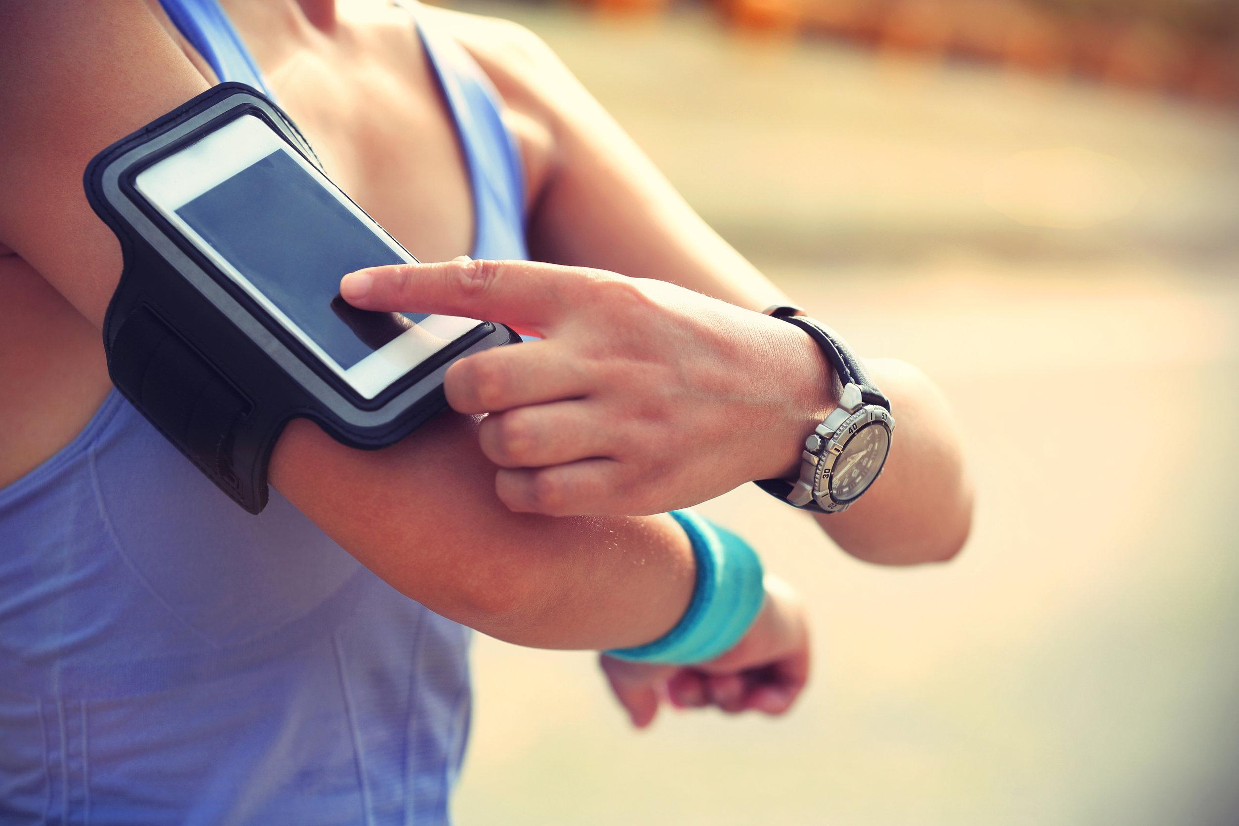 Pessoa com braçadeira mexendo no celular