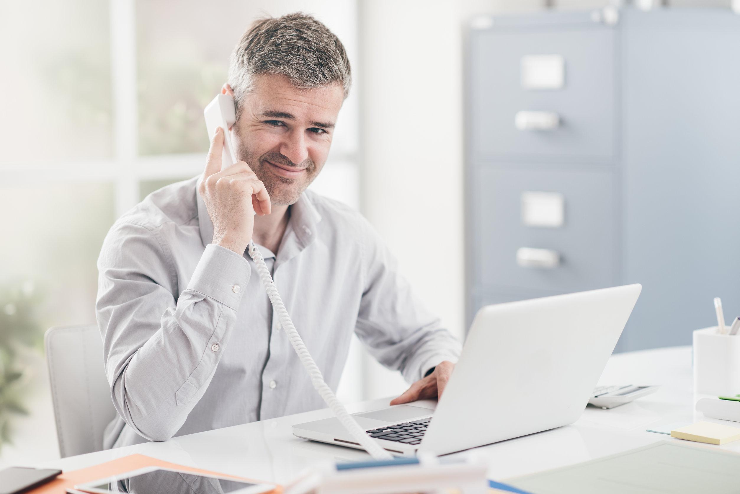 Homem lendo a prescrição de um remédio em uma mesa com computador e vários papéis amassados