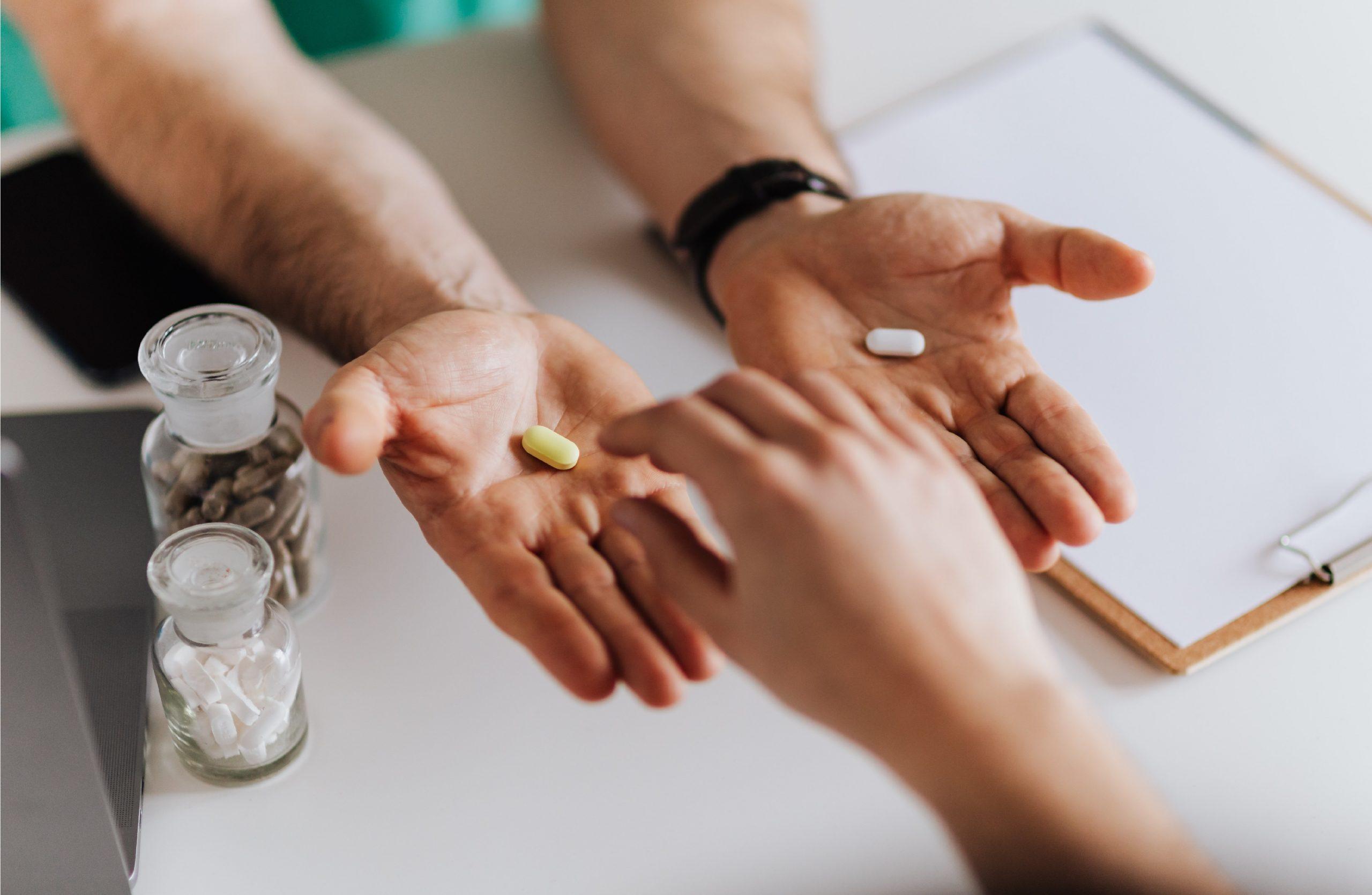 Pessoa com as duas mãos estendidas e em cada uma existe uma cápsula diferente de suplemento