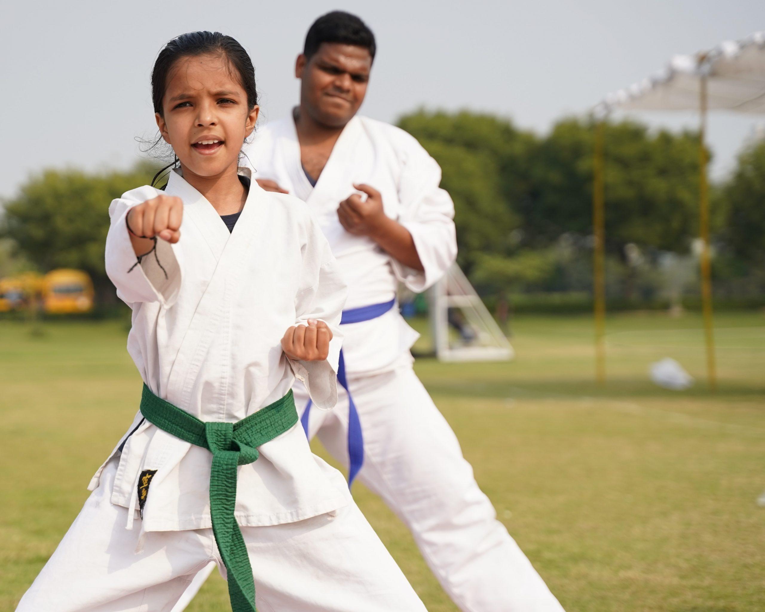 Foto de duas crianças, uma menina e um menino, praticando karatê