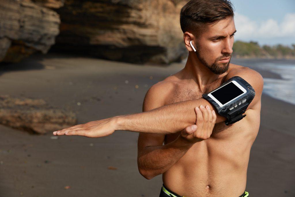 Homem na praia se alongando. Ele usa fones portáteis e seu celular está na braçadeira.