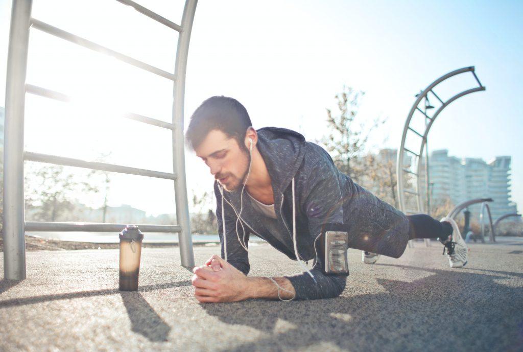 Homem fazendo exercício de prancha na rua. Ele escuta música no celular preso na braçadeira.