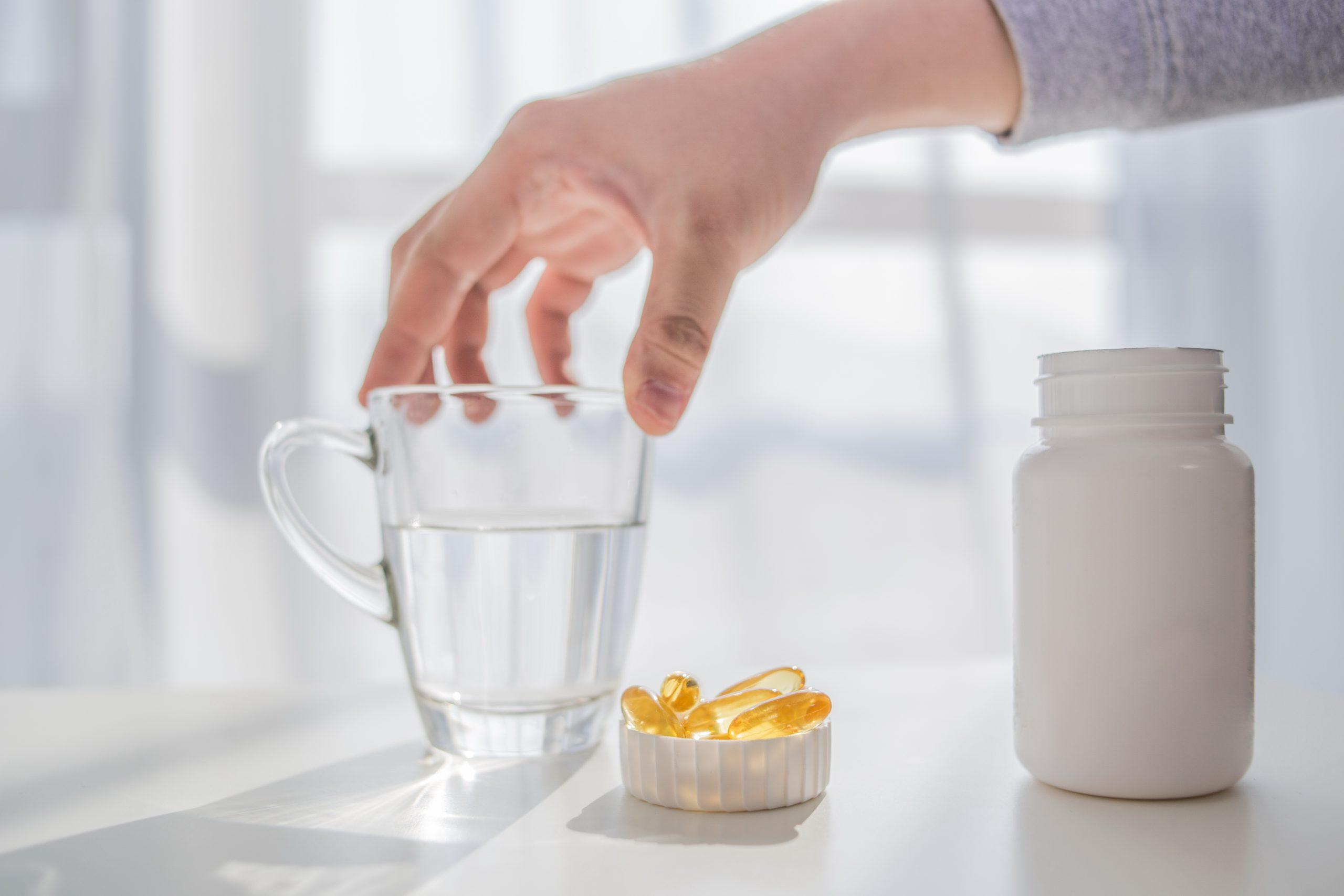 Pessoa com mão sob um copo de água. Ao lado existe um pote de suplemento aberto. A tampa está na mesa com cápsulas dentro.