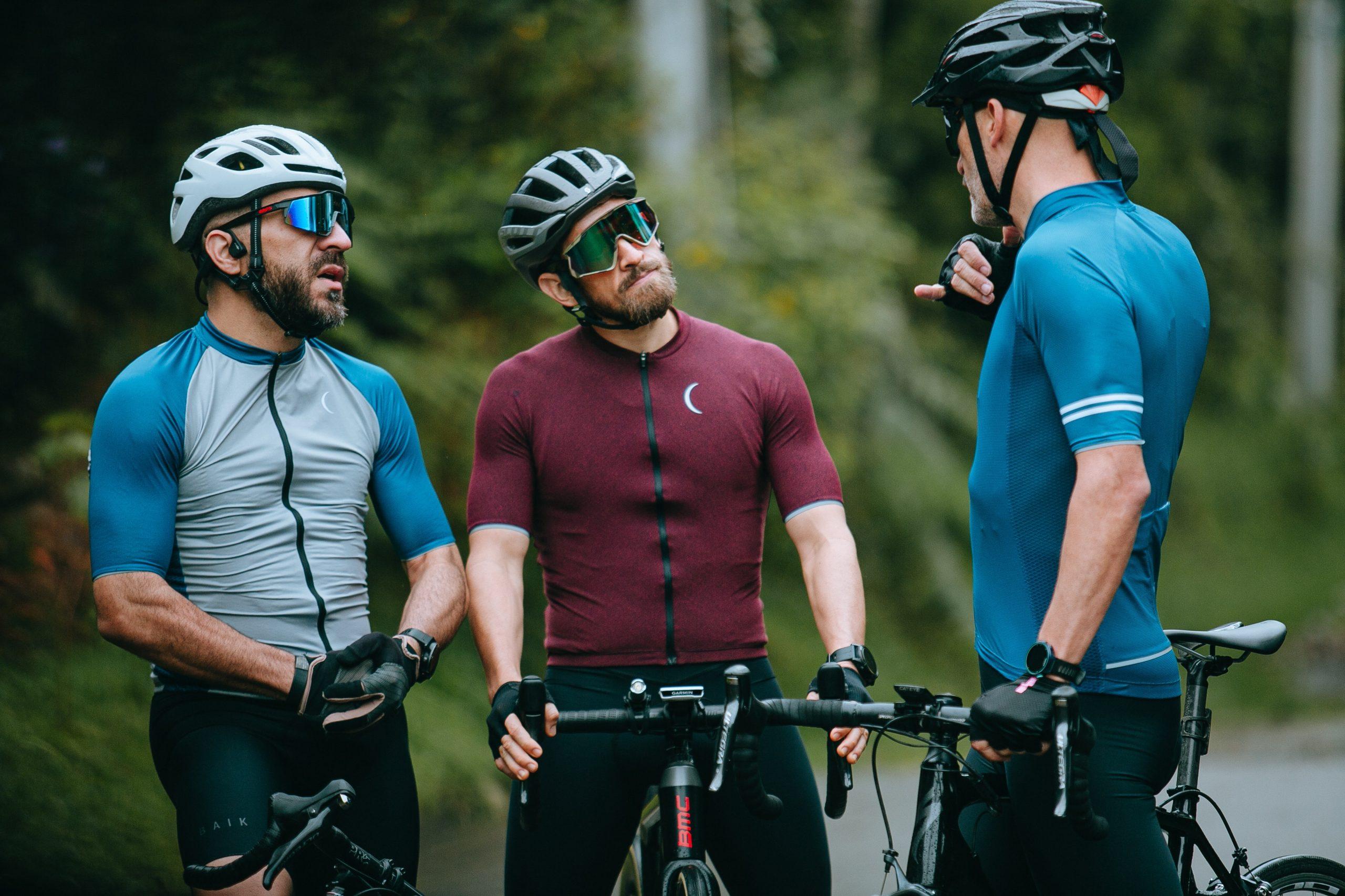 três ciclistas parados em cima da bicicleta conversando. Todos estão com óculos de ciclismo.