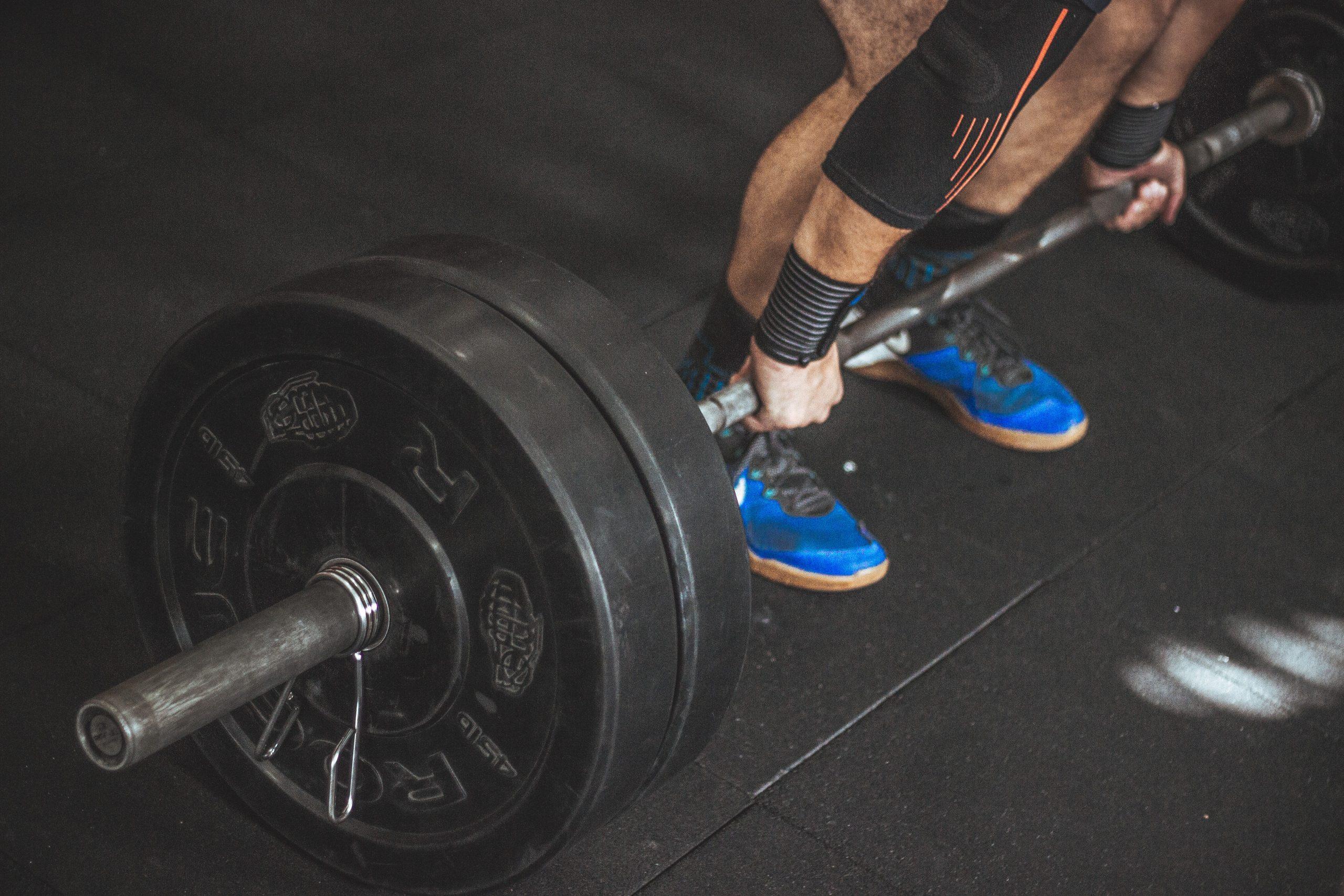 Homem levantando peso na academia com munhequeiras ao redor do pulso