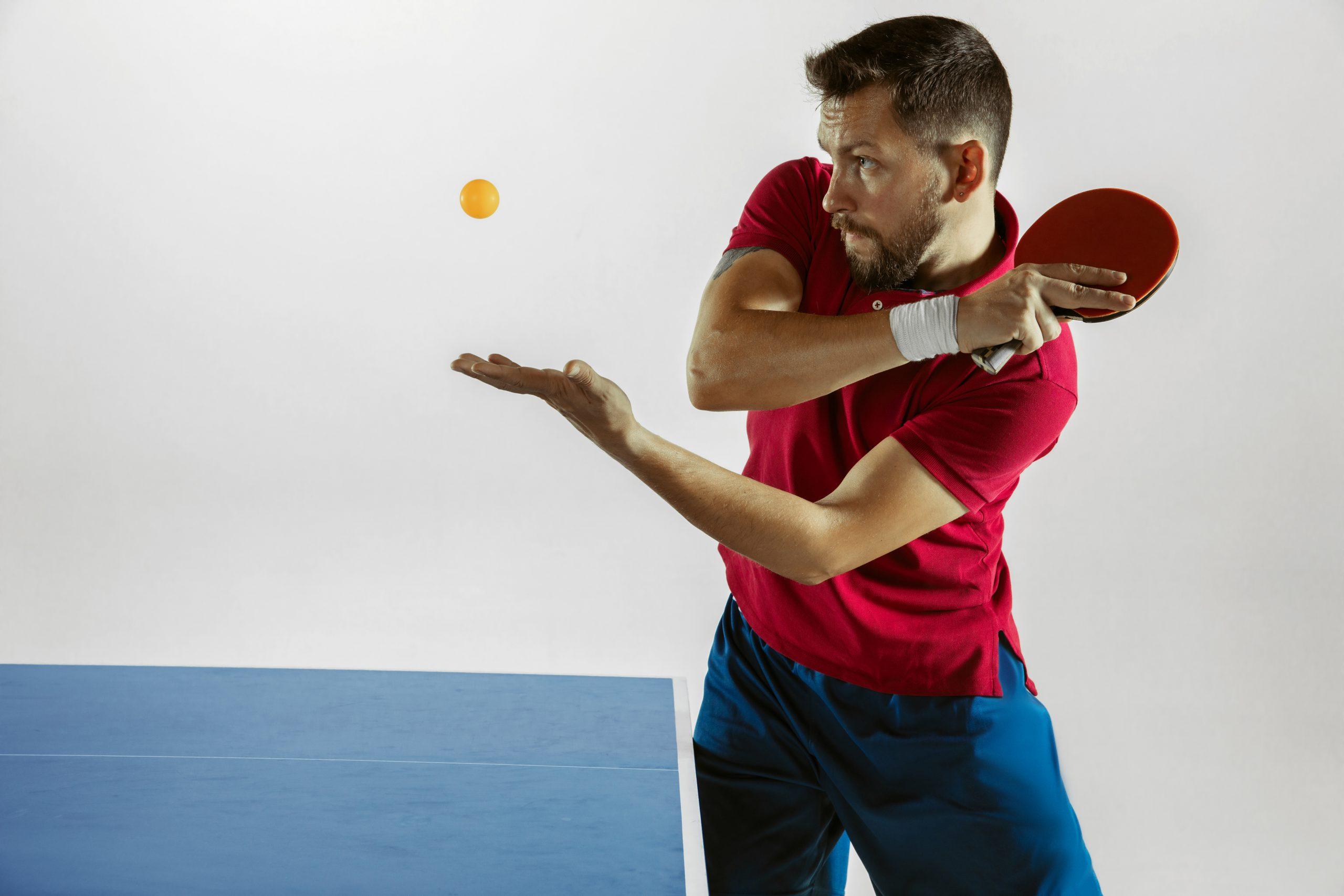 Homem jogando tênis de mesa com bolinha em uma mão e raquete na outra