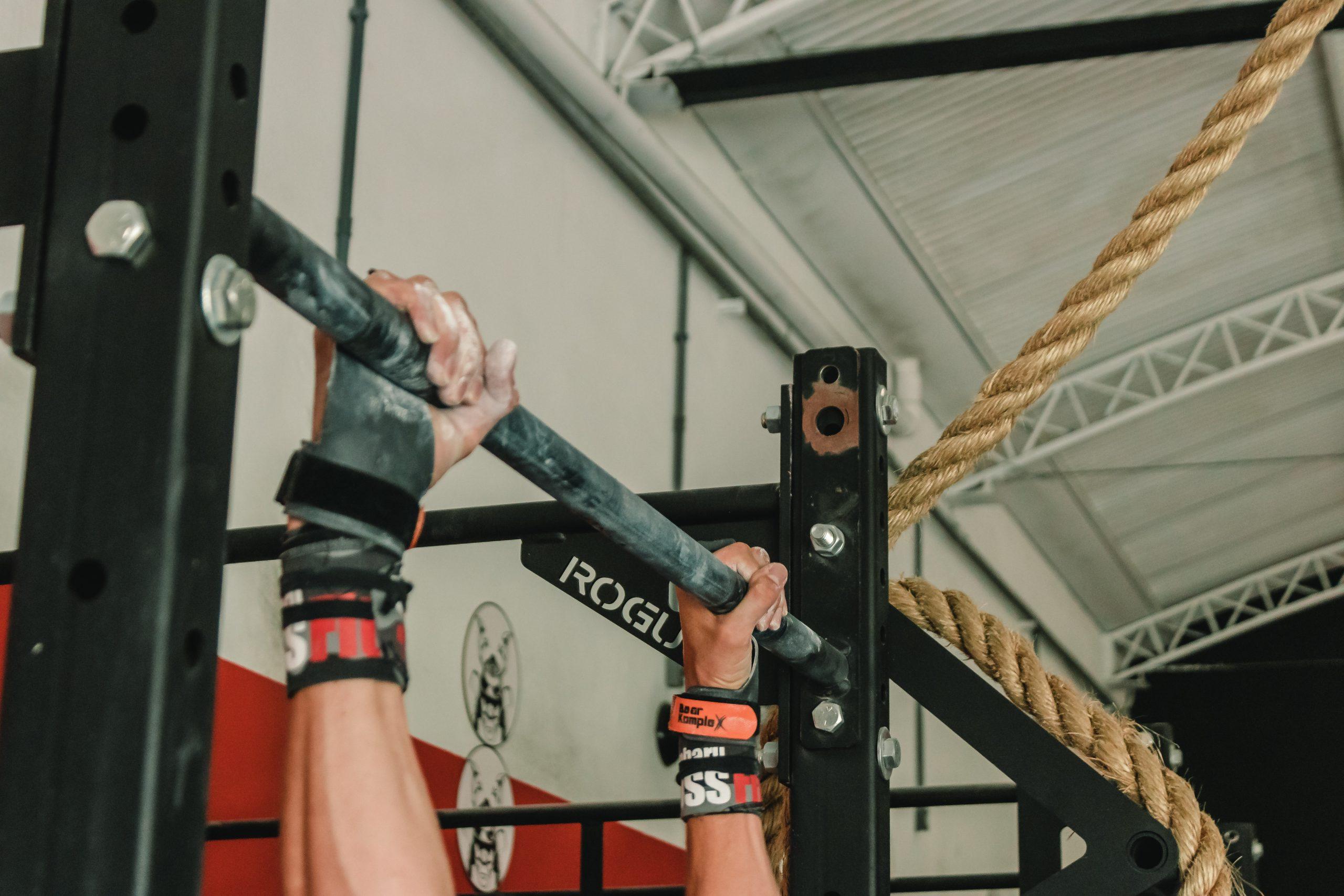 Pessoa fazendo atividade numa barra suspensa com munhequeiras nos pulsos