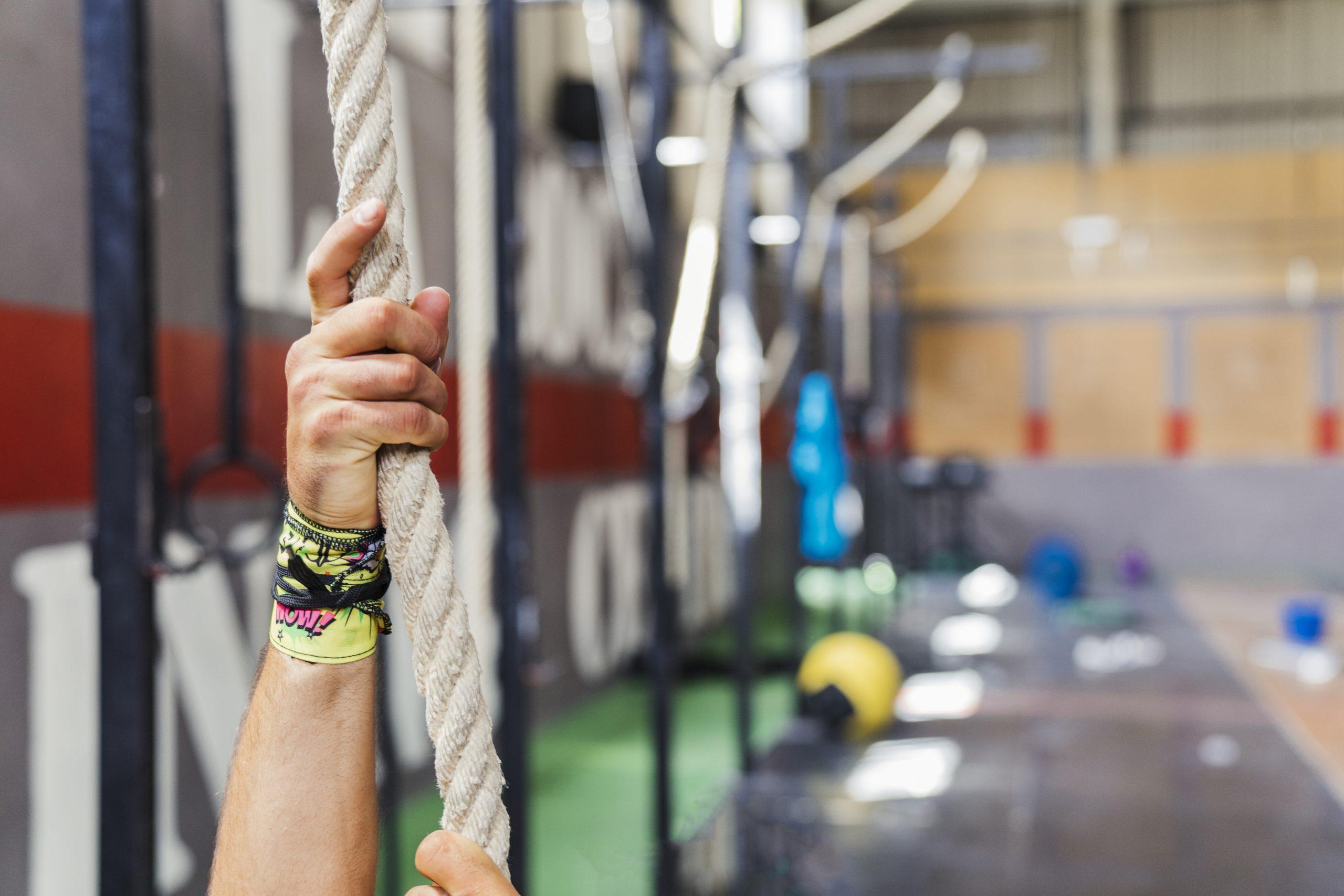 Mão com munhequeira segurando uma corda na academia